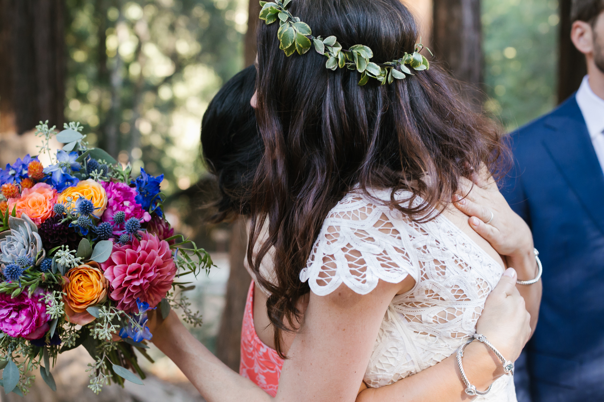 Bride with bright bouquet hugs her family