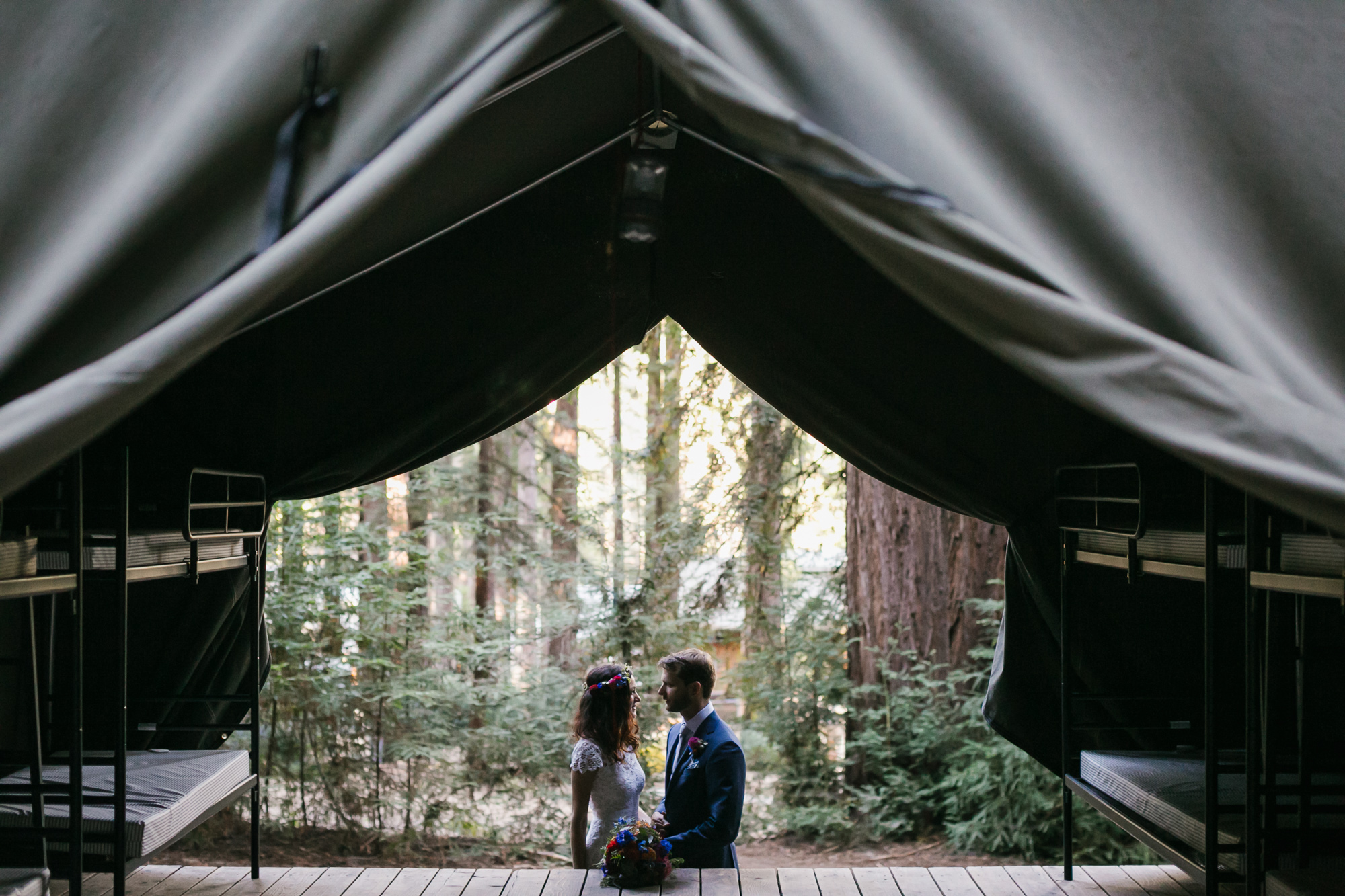 Silhouette of wedding couple as seen through a green canvas tent flap