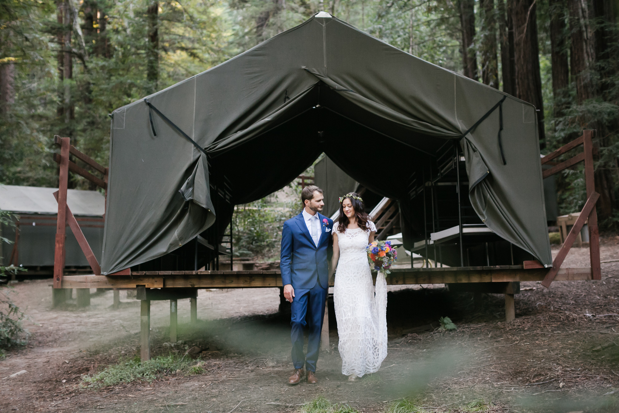 Bright wedding couple stand in front of green canvas tent cabin