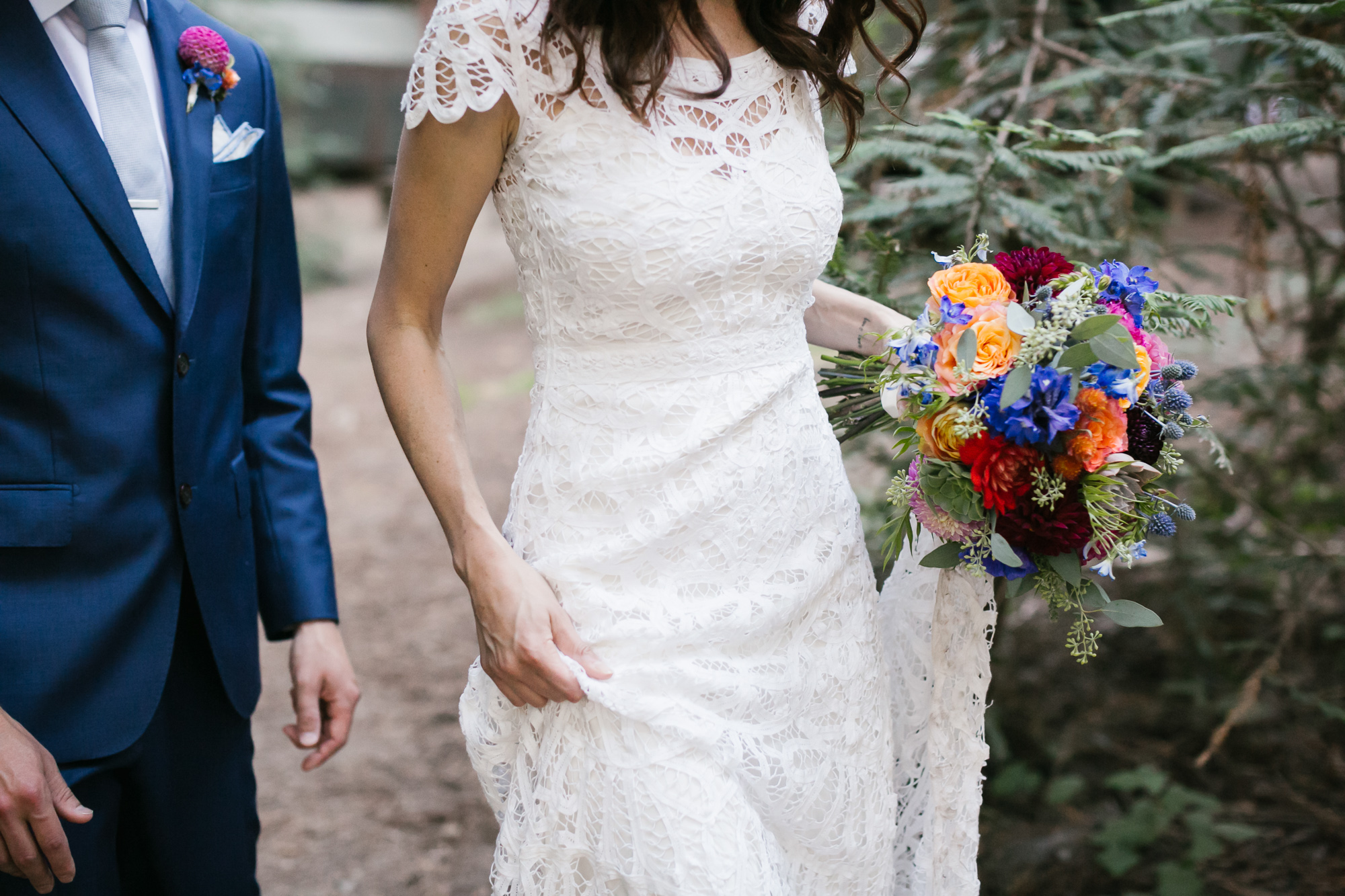 Bride holds her lace gown and bright bouquet as she walks with her husband in his blue suit