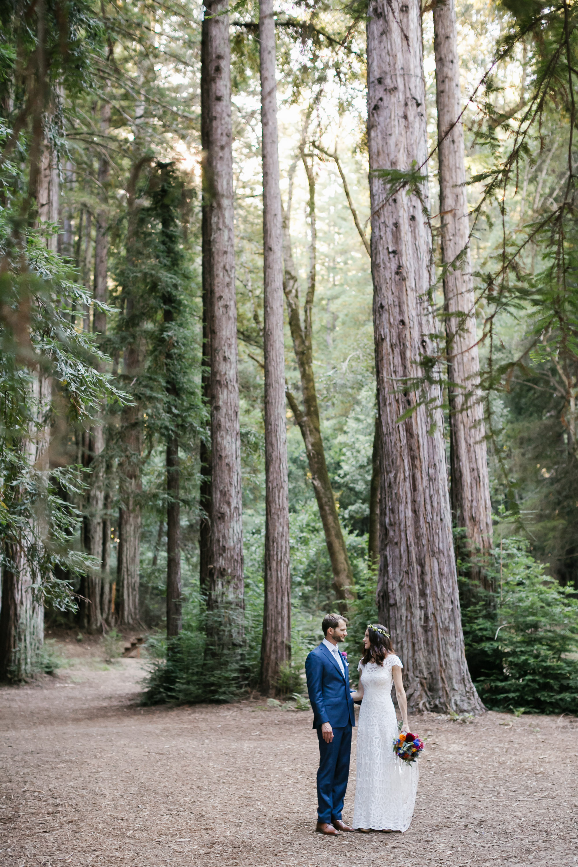 Bright wedding couple stand together in a redwood forest