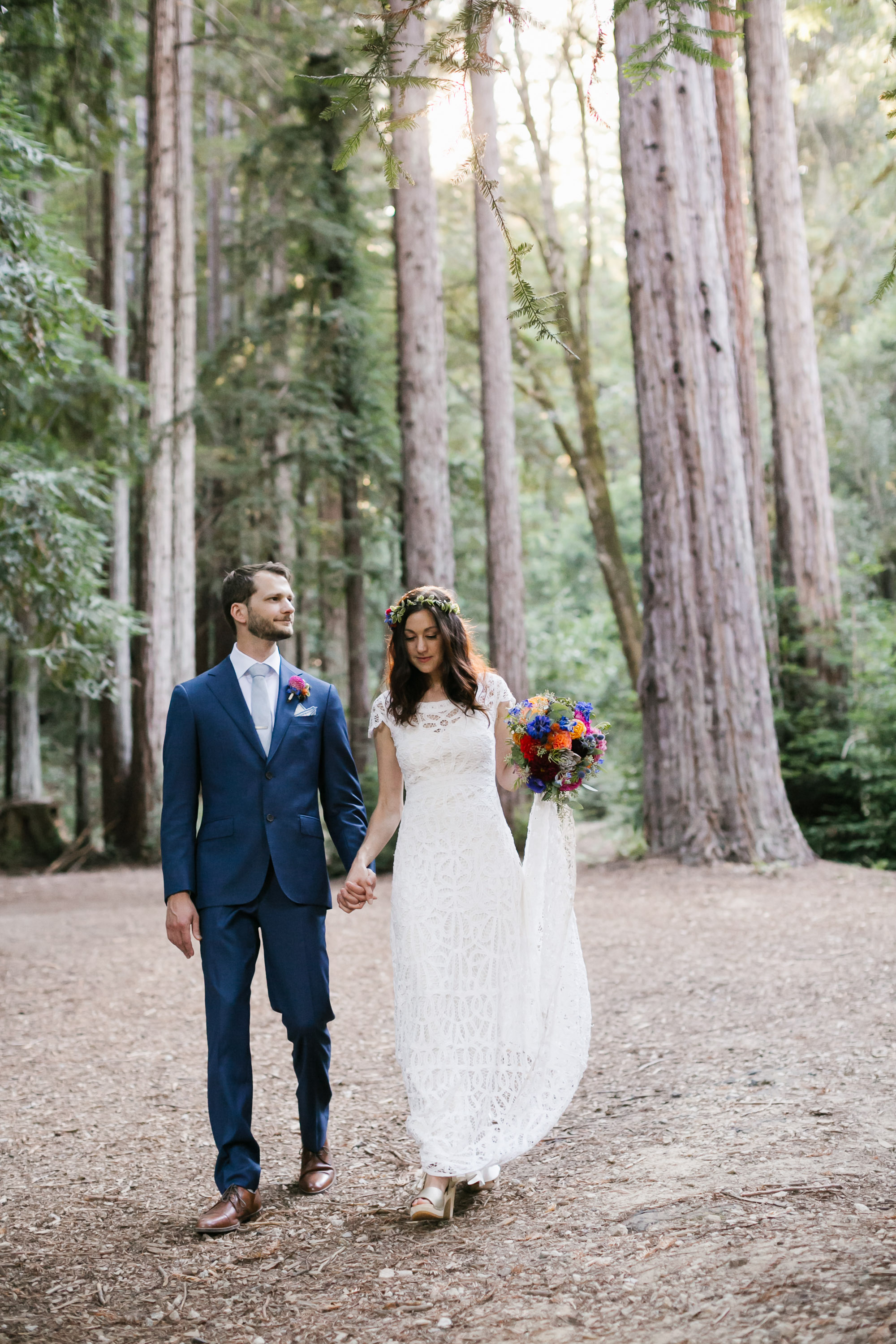 Wedding couple hold hands walking through the forest