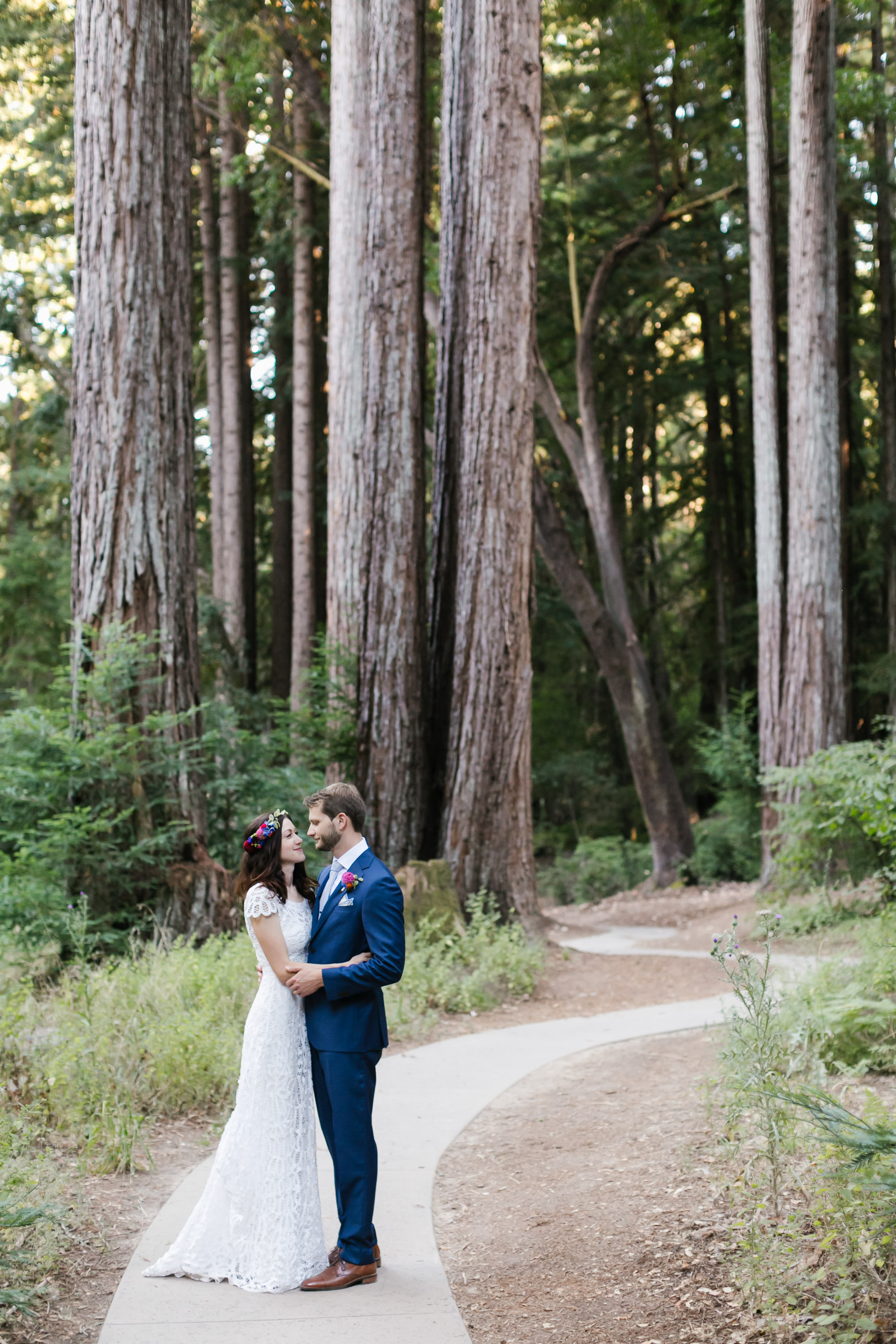Wedding couple hold each other on winding path through the trees