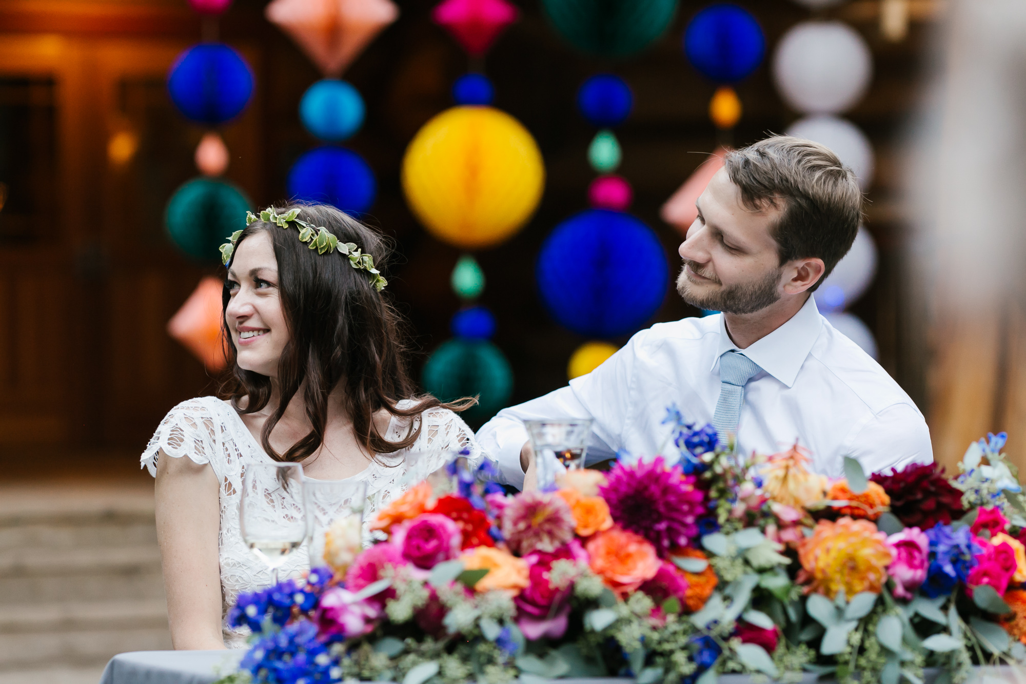 Bride and groom enjoy speeches during their colorful outdoor wedding reception