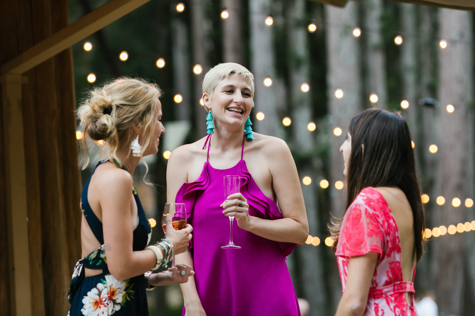 Colorfully dressed guests enjoy cocktails at outdoor camp wedding