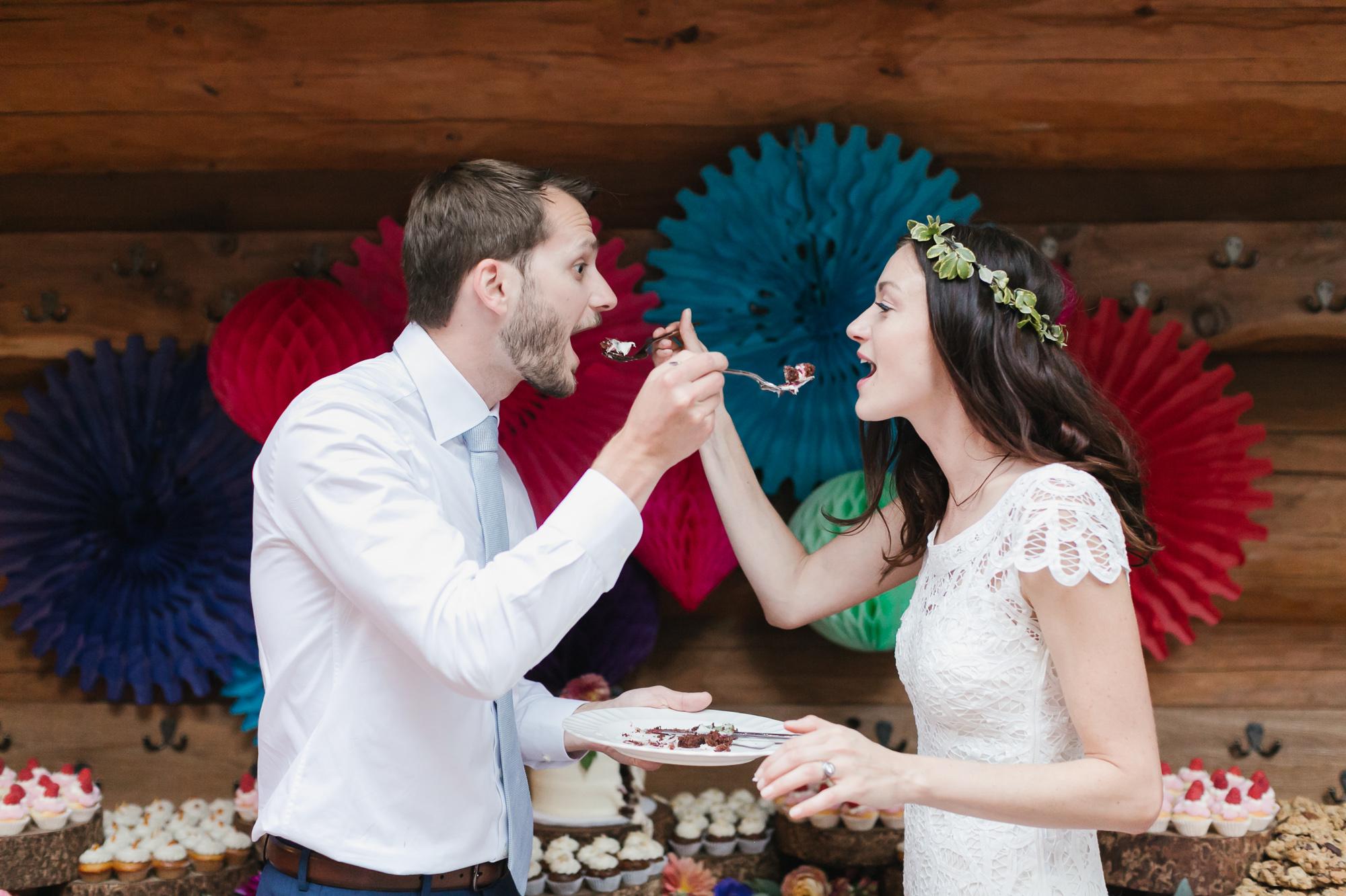 Wedding couple exchange bites of their wedding cake
