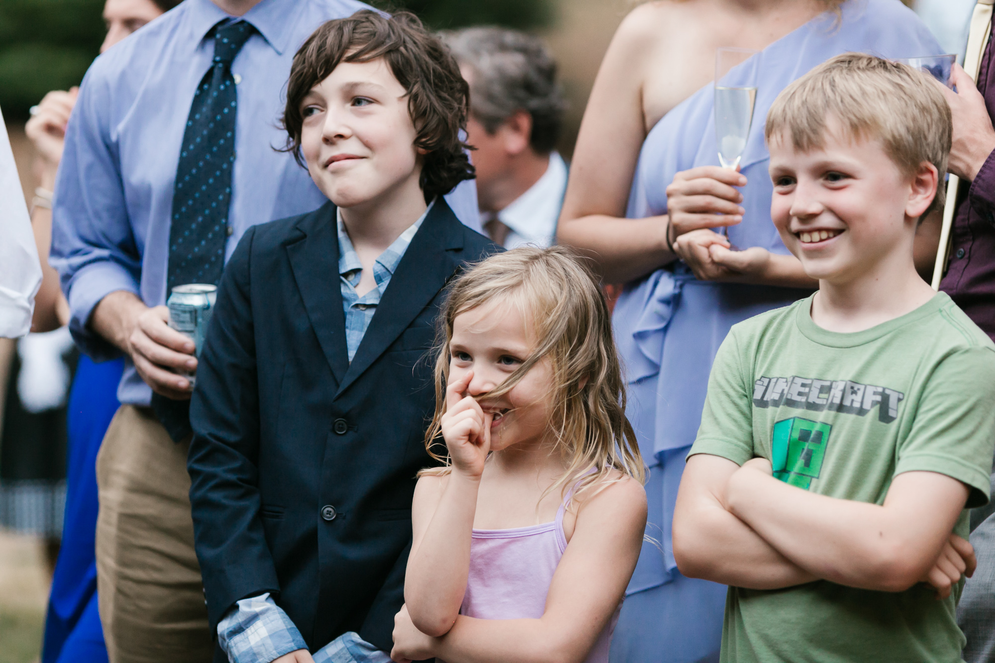 Kids at wedding happily watch couple cut their cake