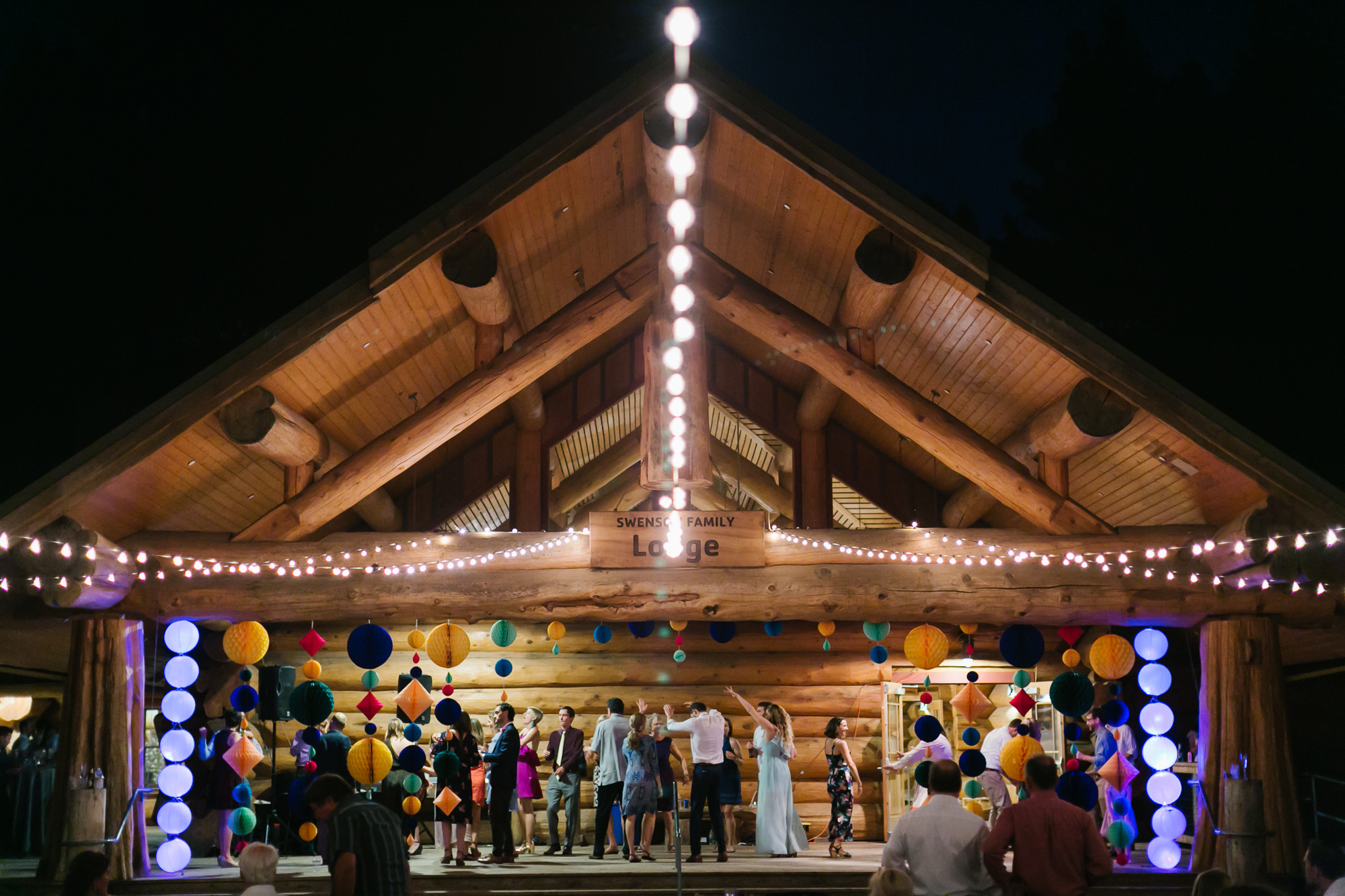 Night time scene of the log cabin lodge where the wedding dance party continues