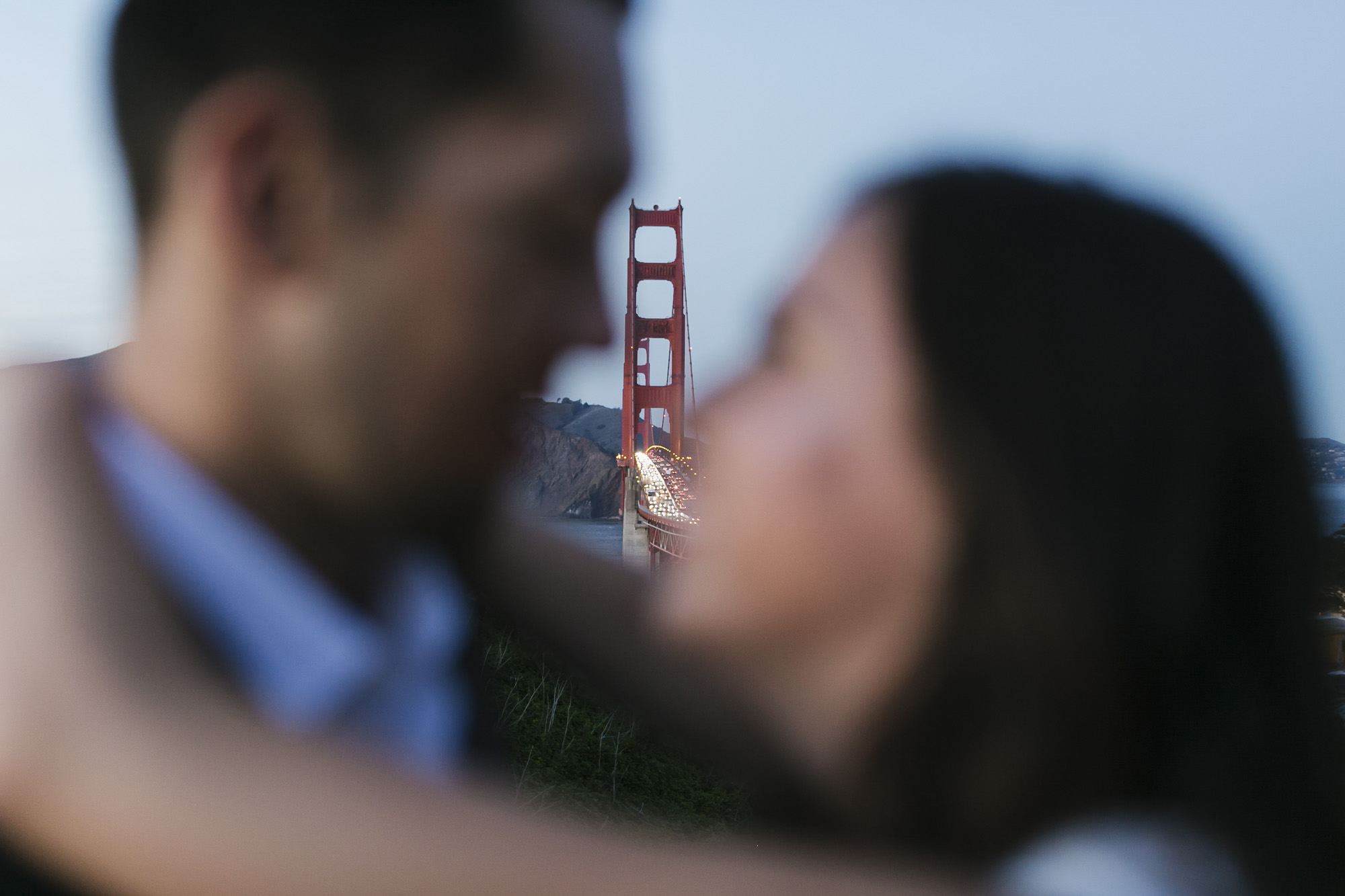 Couple hugging in front of the Golden Gate Bridge at sunset