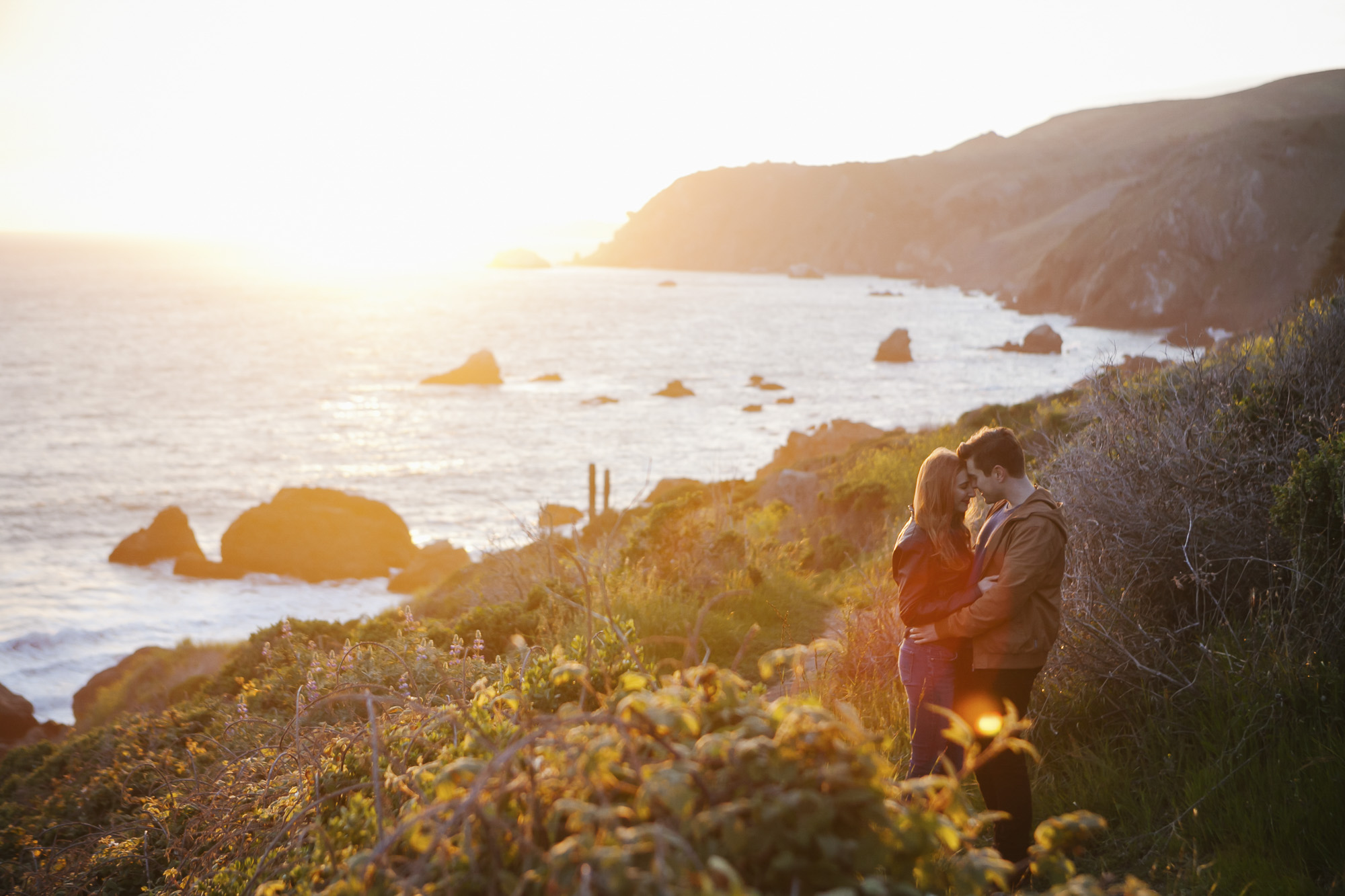 Couple embrace at sunset on the coast of Northern California at Slide Ranch