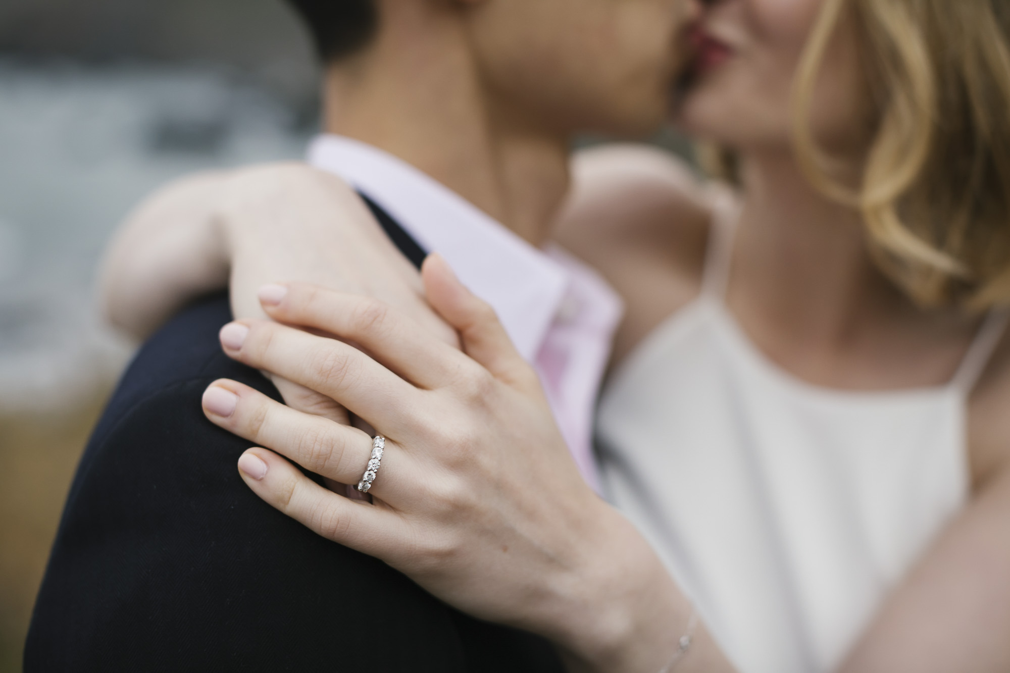 A wedding couple kiss in the background of a detail shot of her wedding ring