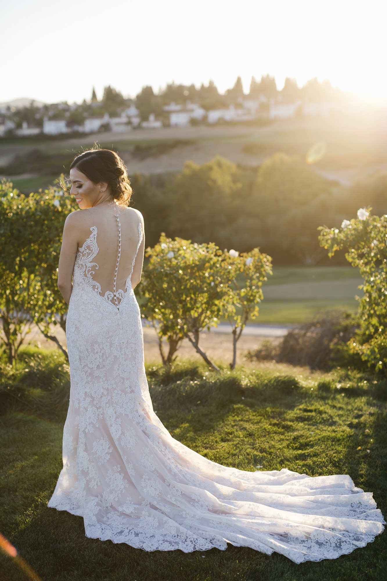 A bride shows off the back of her wedding dress in a garden at sunset
