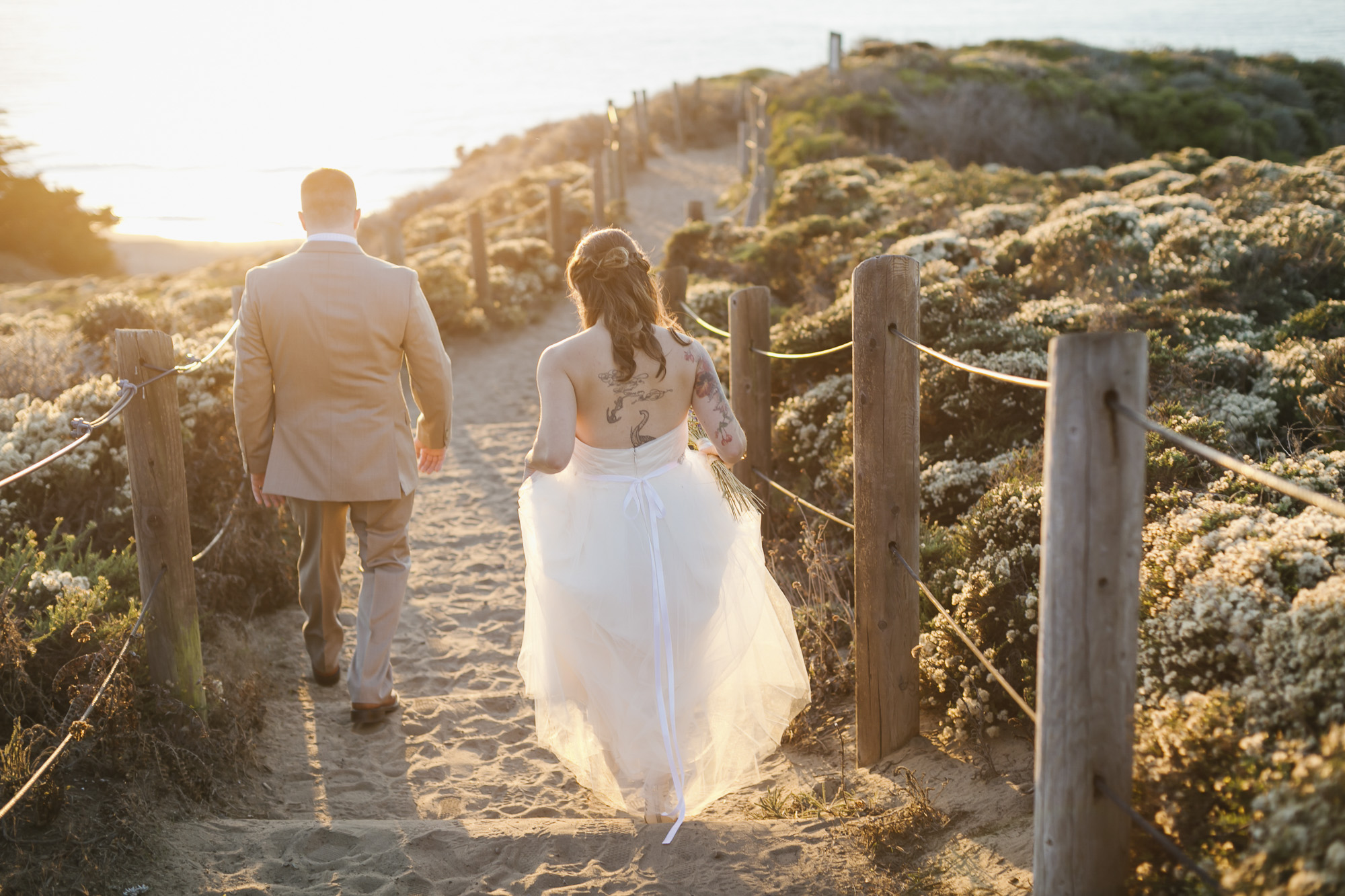 A wedding couple walk into the sunset together