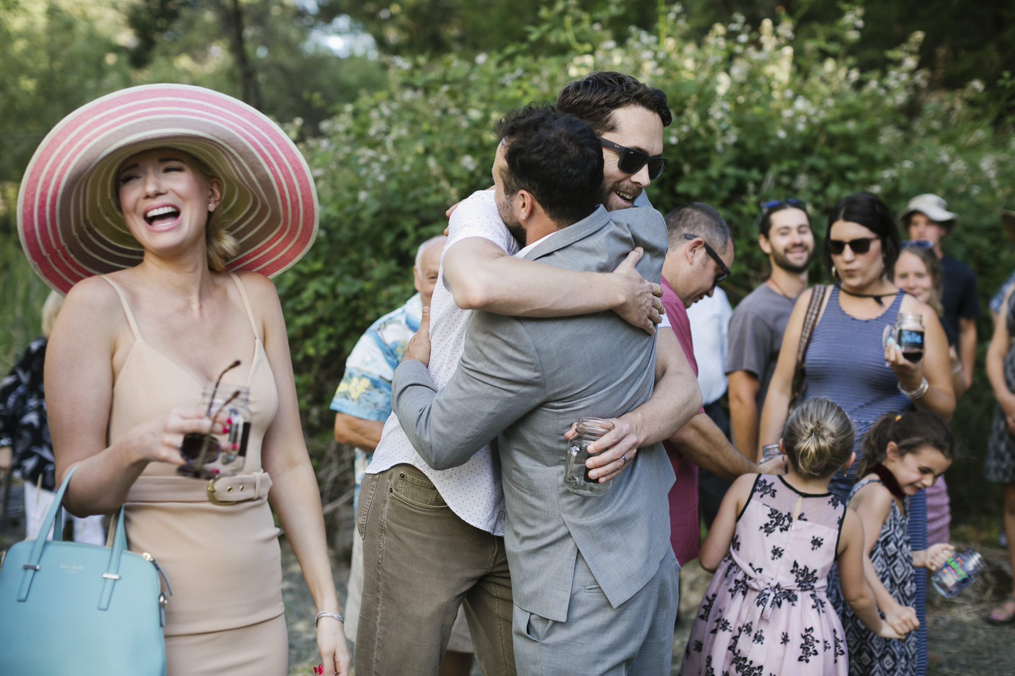 Groom hugs his friend among other happy guests