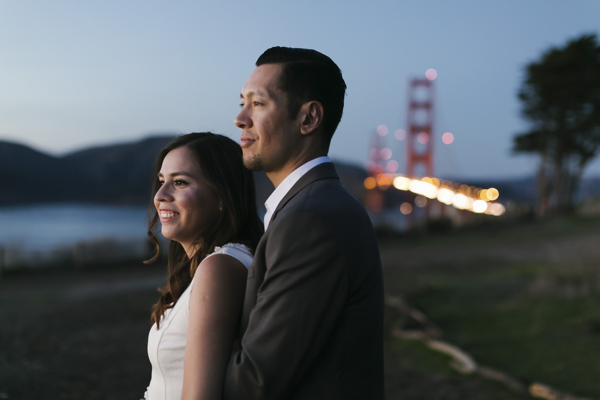 Engaged couple look out at the sunset with the Golden Gate bridge behind them