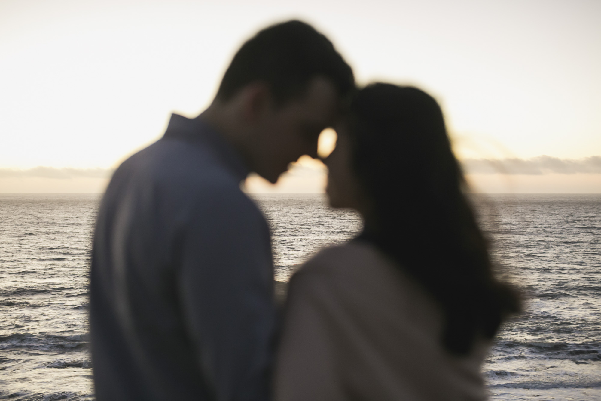 Couple touch foreheads with ocean in the background