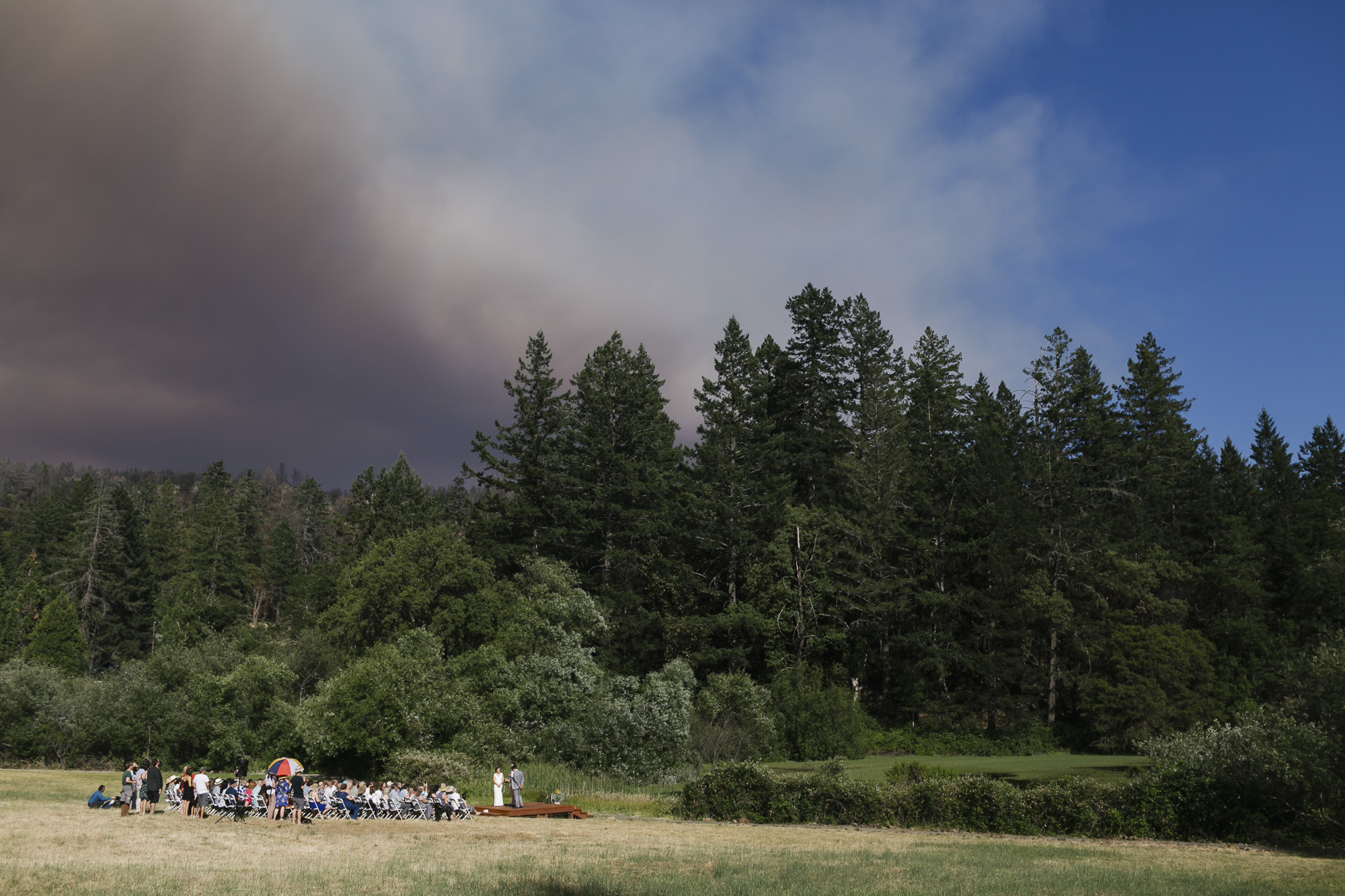 Sunny wedding ceremony in a field with wildfire smoke approaching