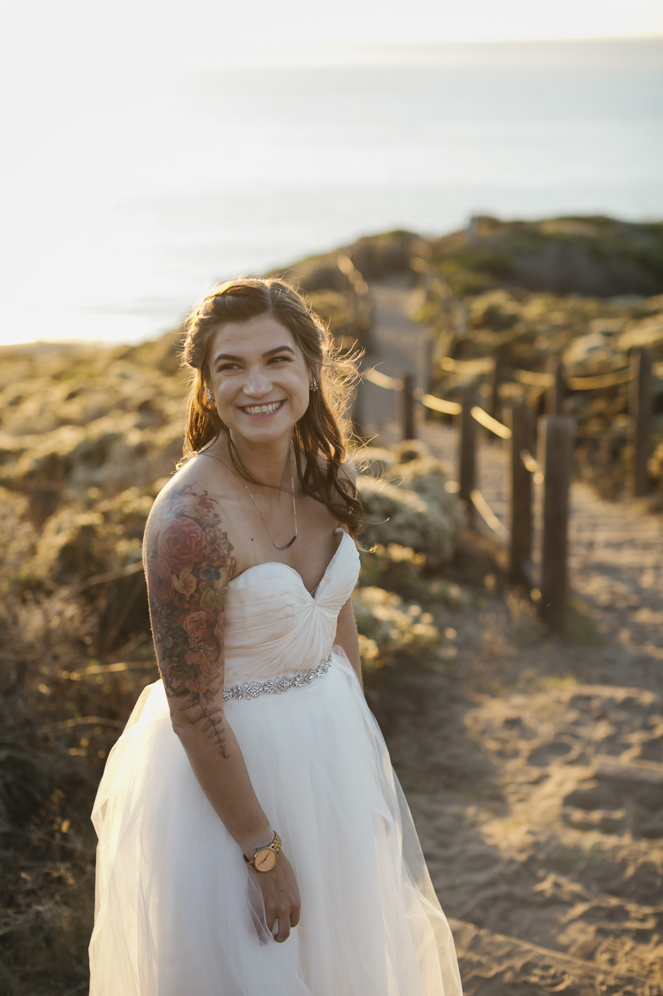 A tattooed bride smiles on her wedding day in the afternoon light at Baker Beach in San Francisco