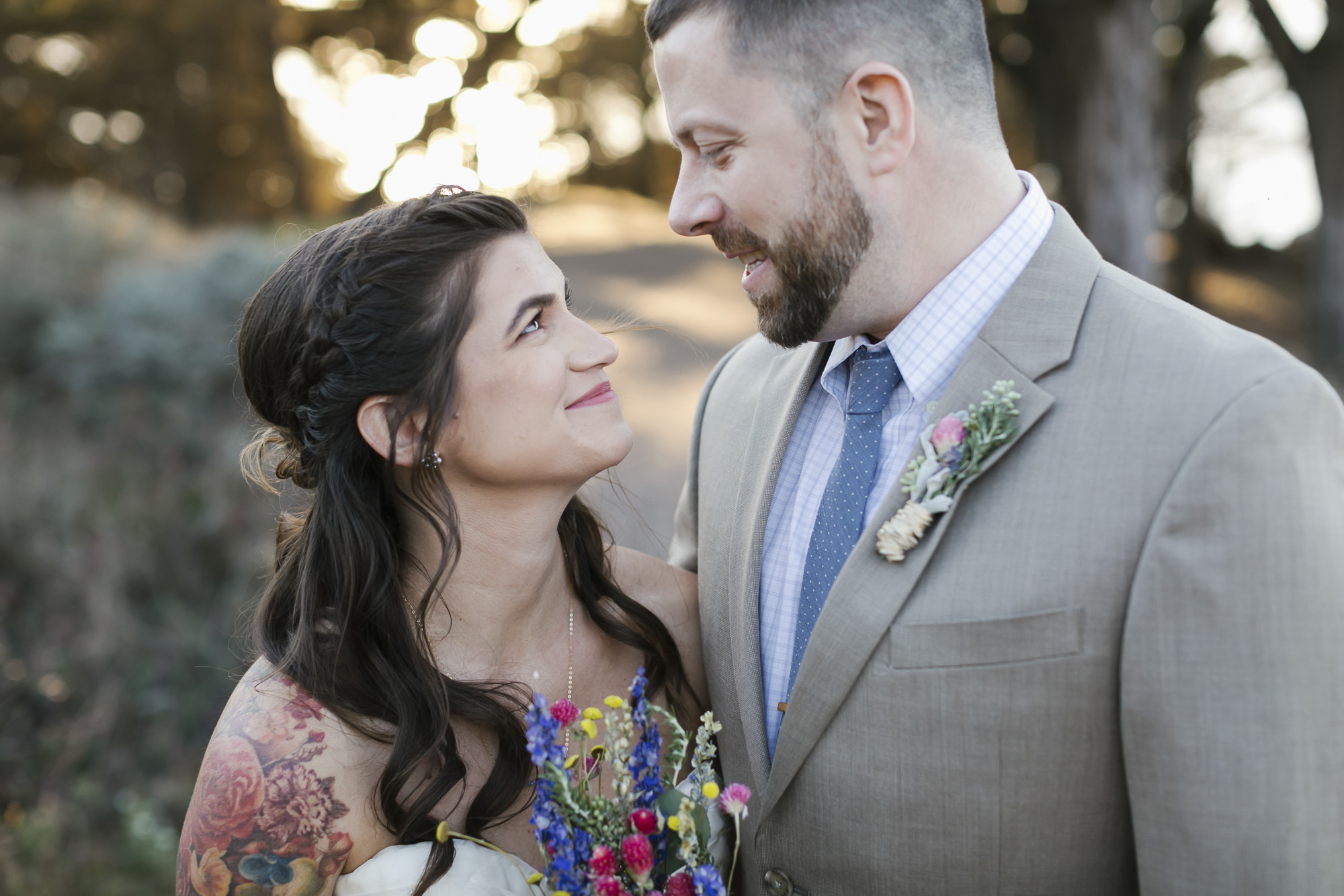 A tattooed bride with a dried flower bouquet gazes lovingly at her husband