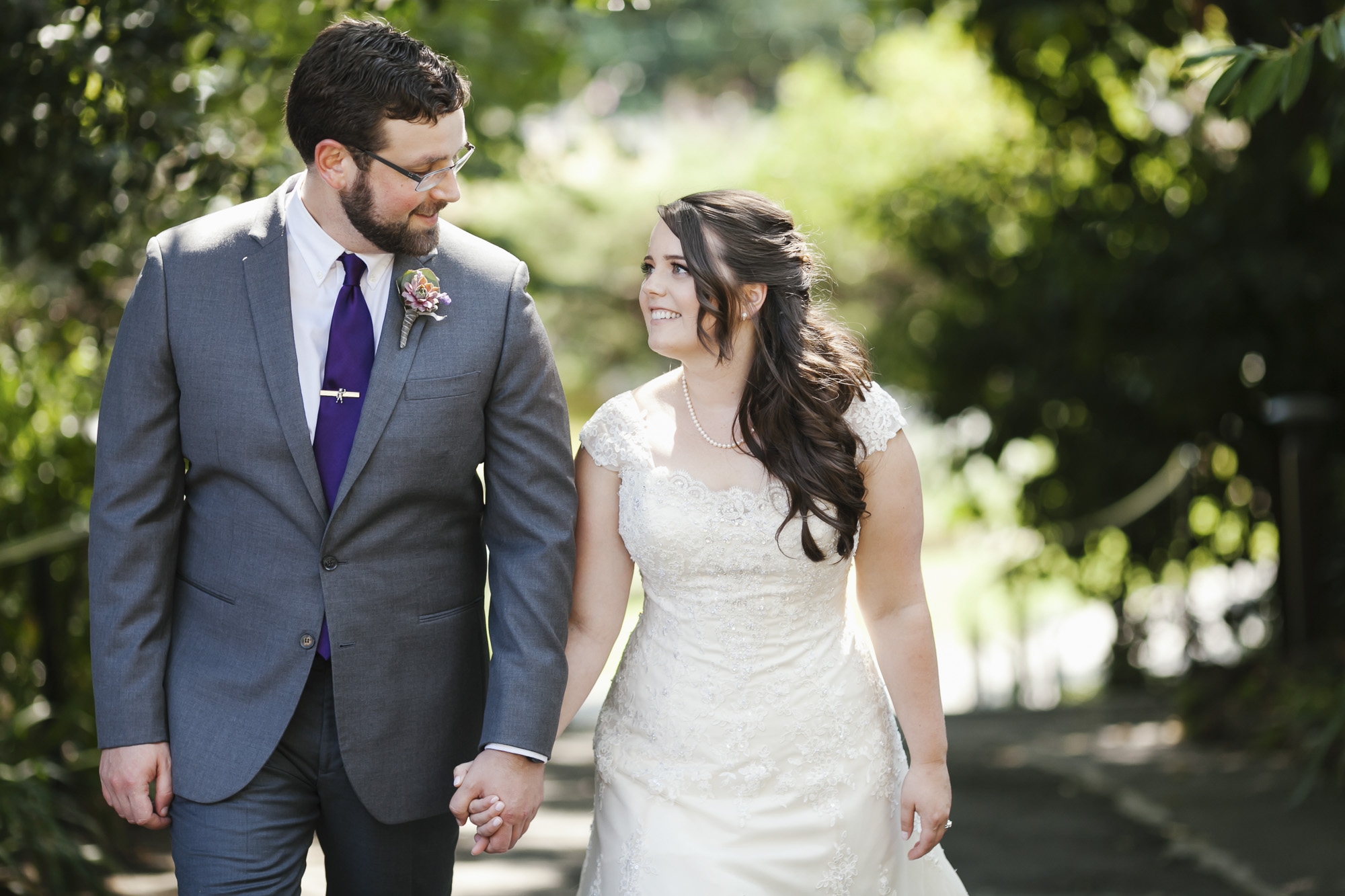 Wedding couple walks together while looking at each other in a garden