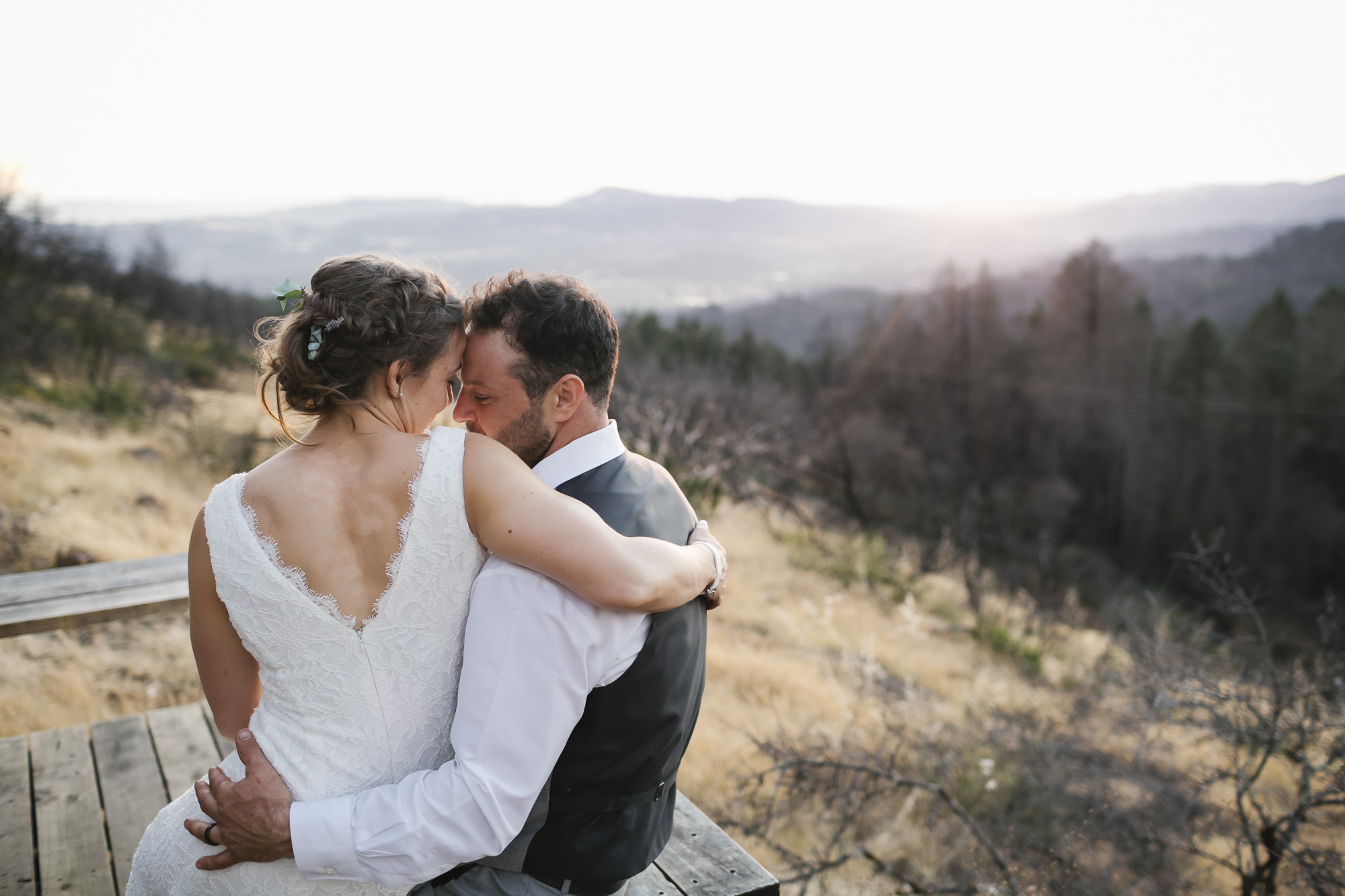 Bride sits on her husband's lap at sunset with wildfire damage behind them