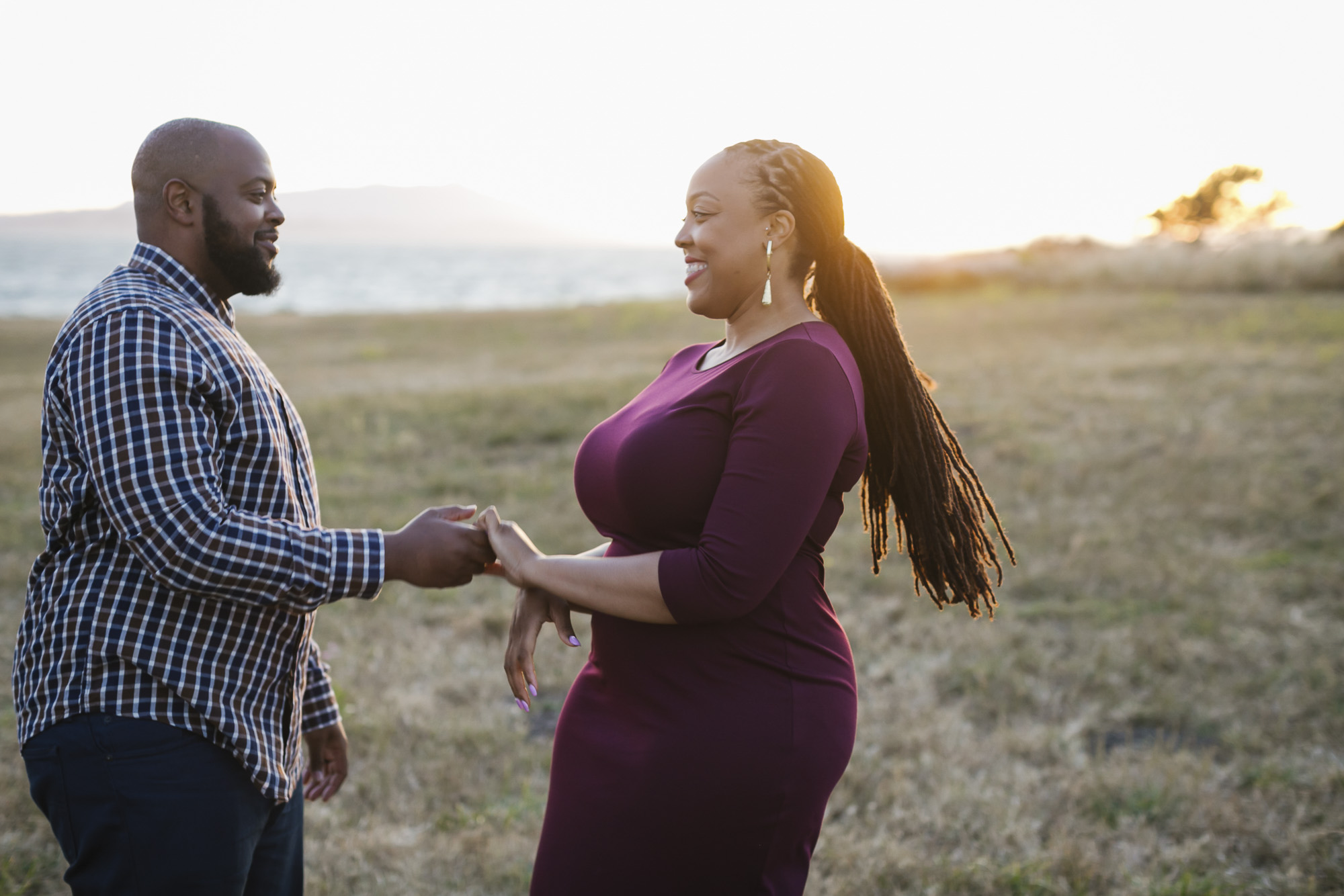 An engaged couple dance together at sunset in Berkeley, she has braids and a purple dress