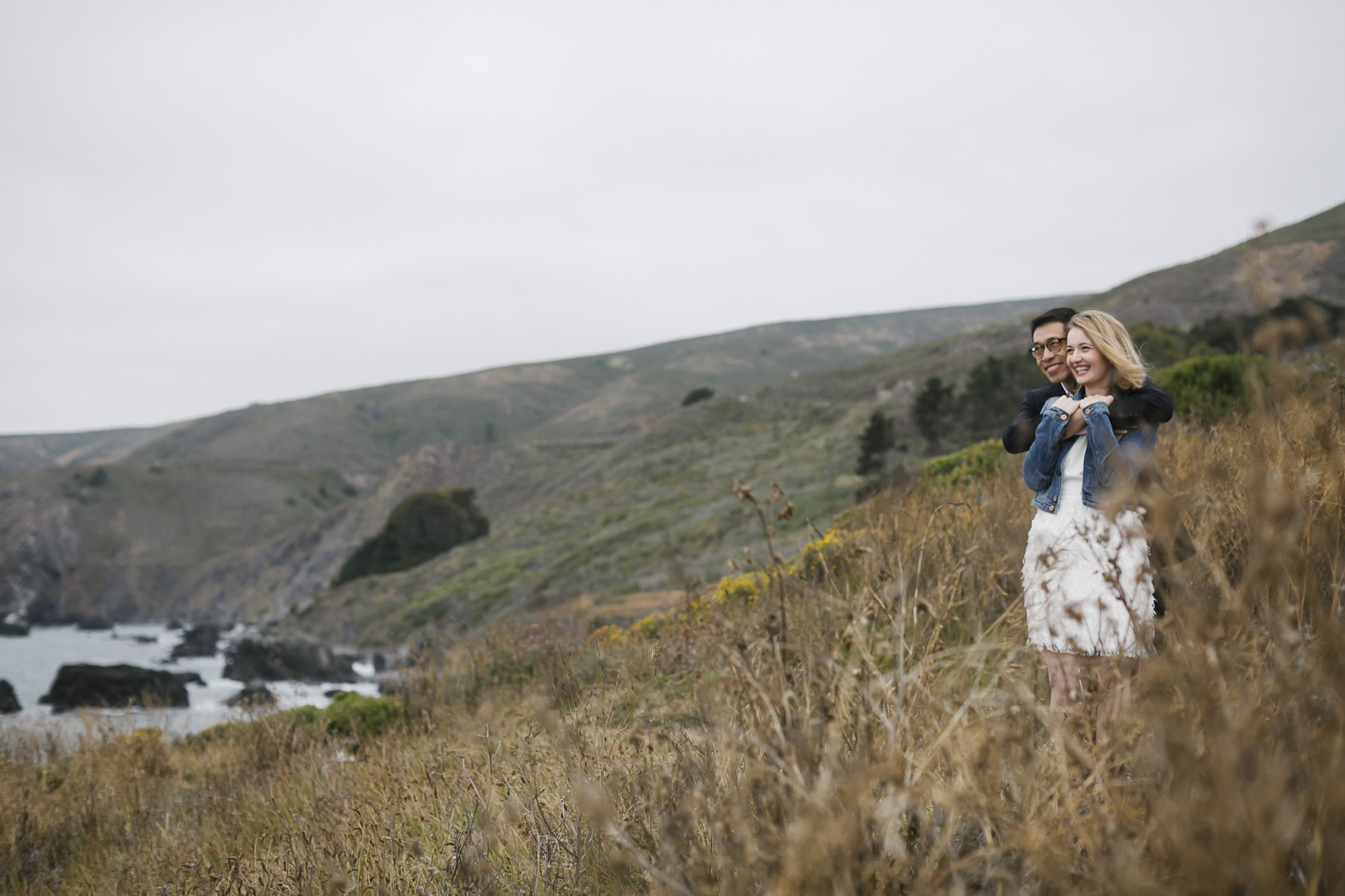 On a coastal hillside, a man hugs his fiancé from behind while looking out at the ocean