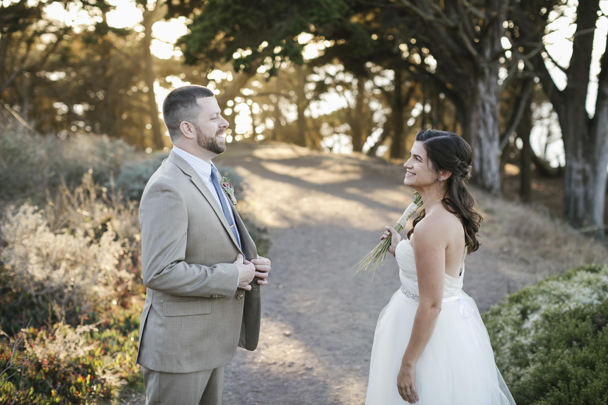 Wedding couple smile at each other as the sun sets behind trees at Baker Beach