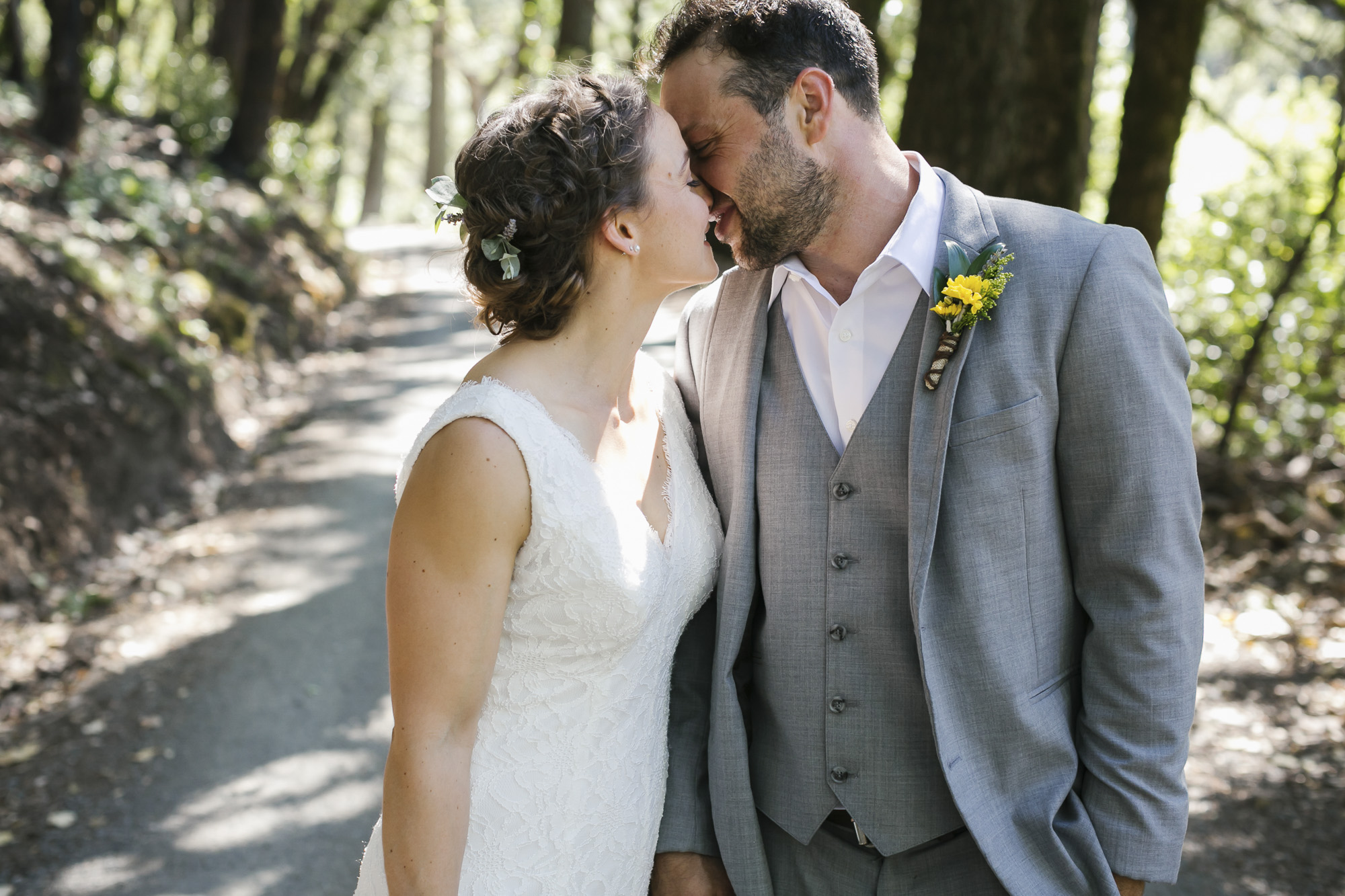 Wedding couple kiss on tree lined lane in Sonoma