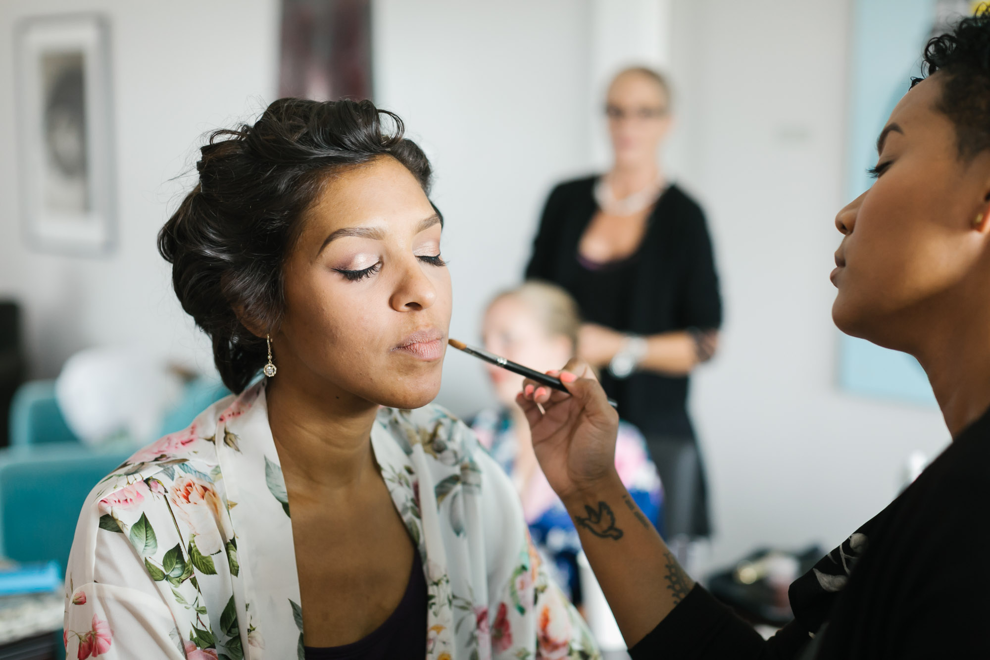 Bride gets her makeup done wearing white floral robe