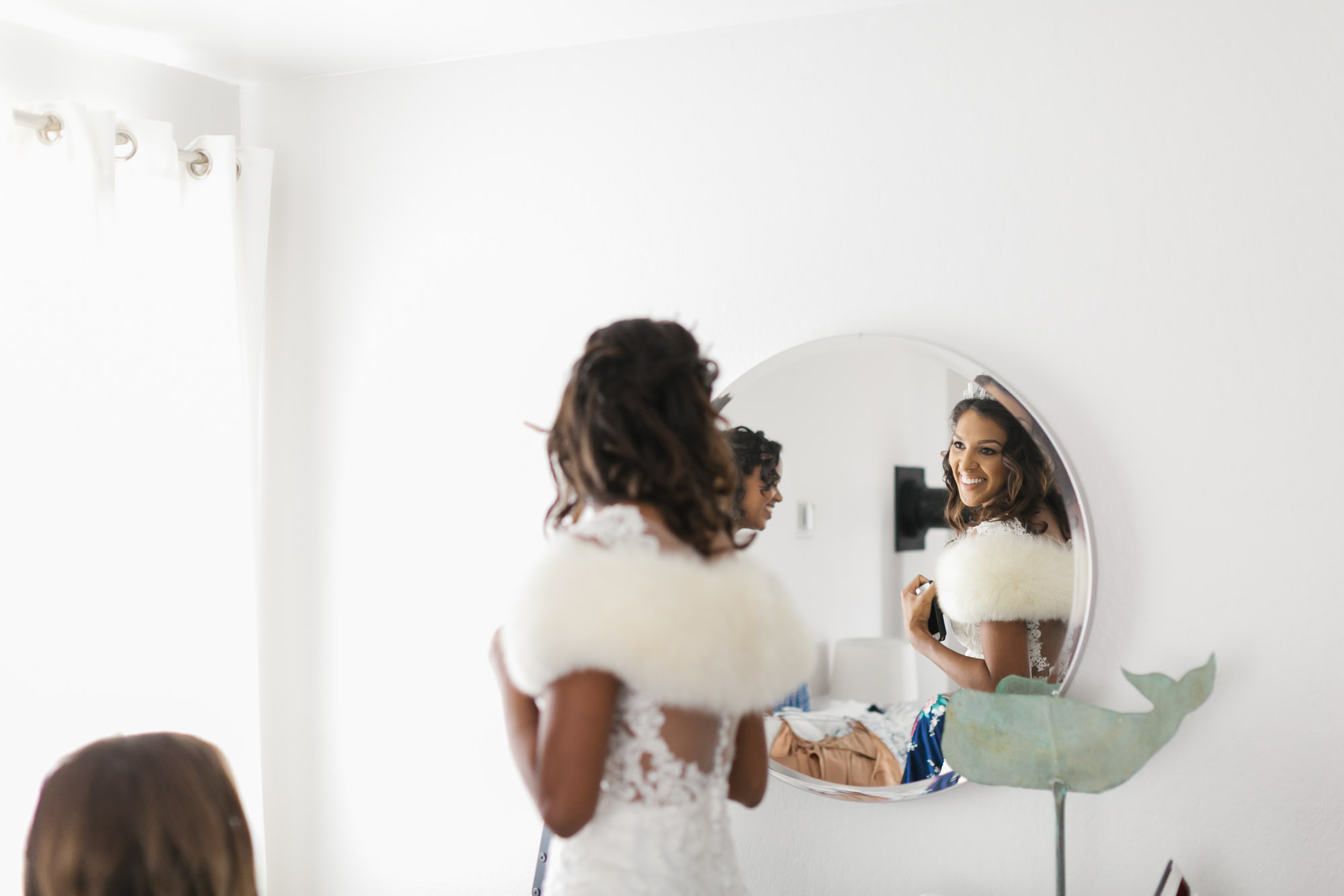 Bride smiles at her reflection in round mirror