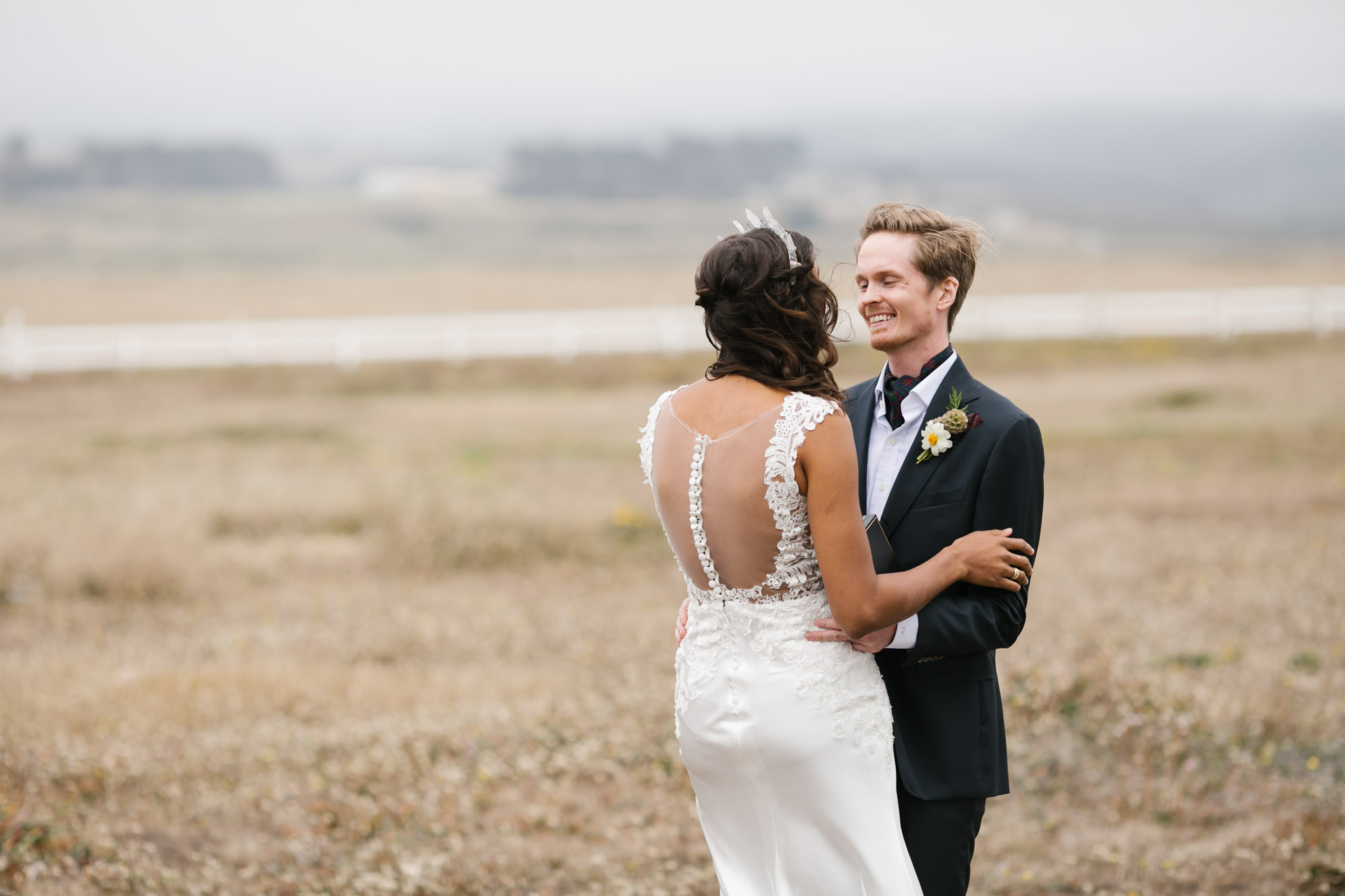 Groom smiles at his bride in a field on the California coast