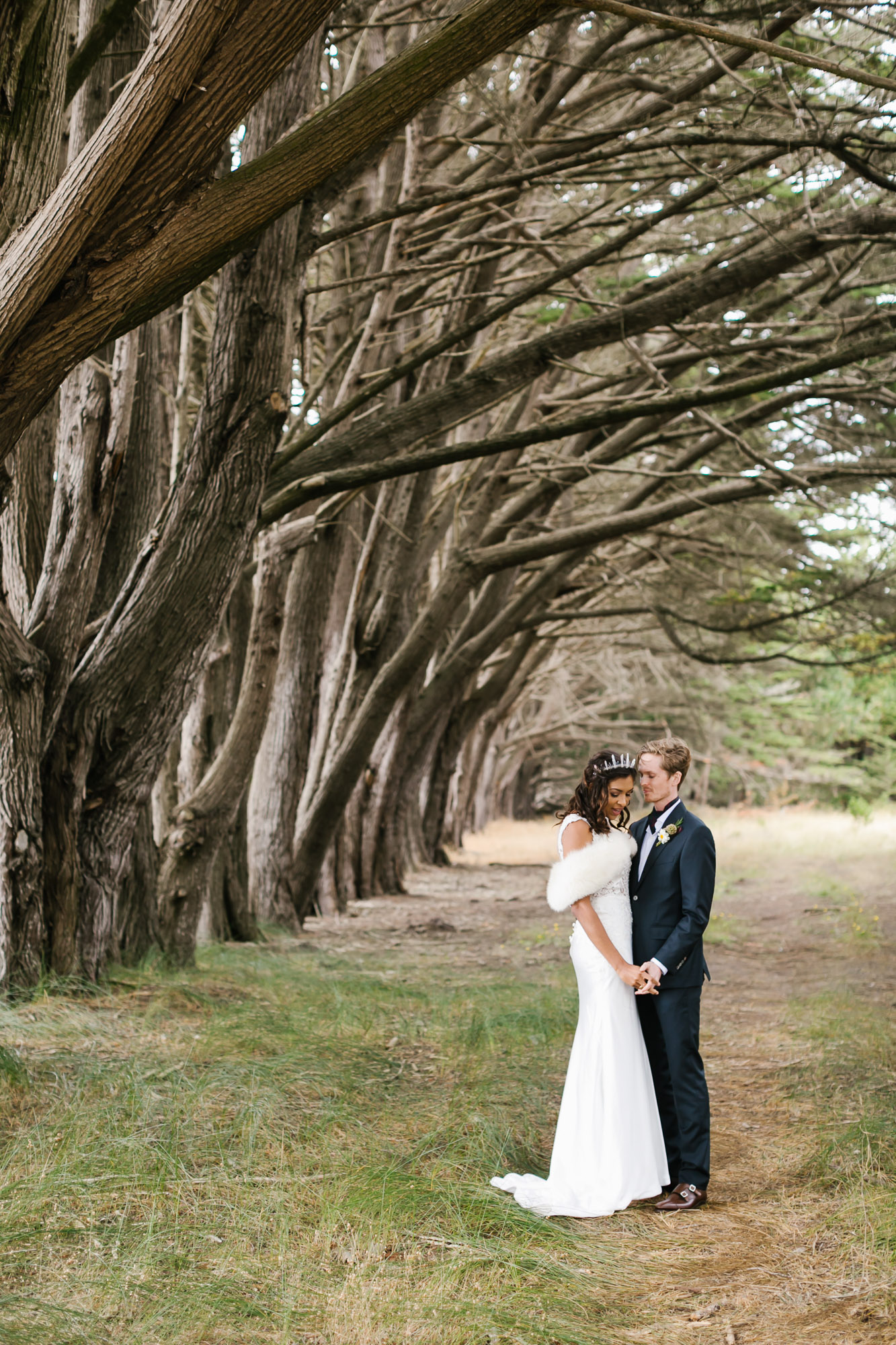 Bride wearing crystal crown stands with groom among coastal trees
