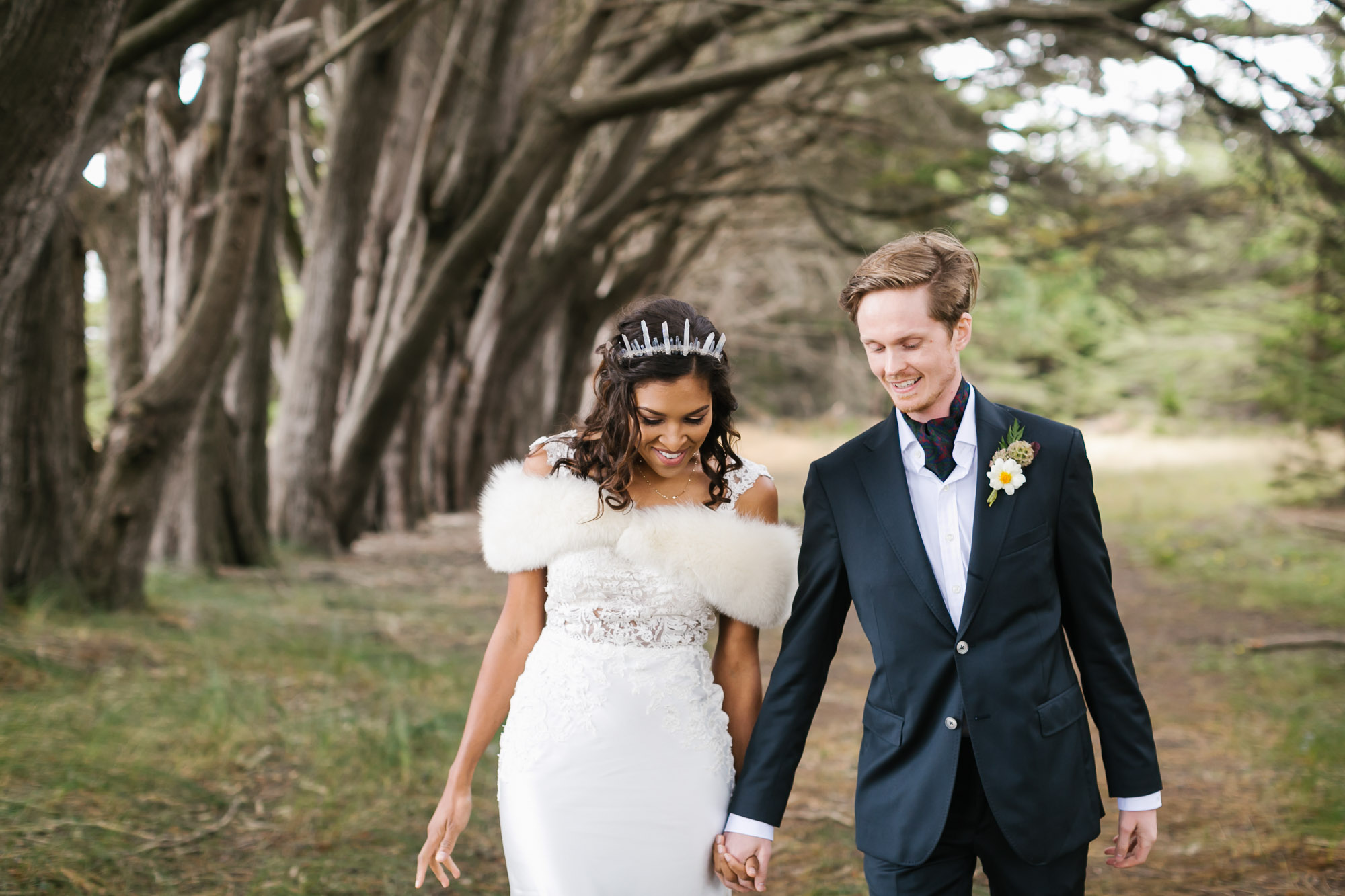 Bride wearing crystal crown and white fur stole walks holding hands with her husband