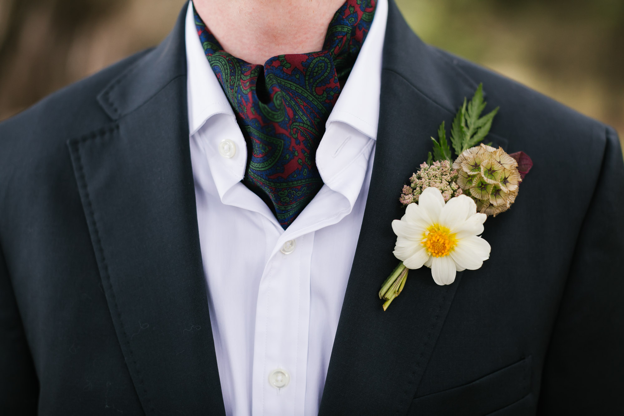 Groom's wedding suit with paisley ascot and boutonniere