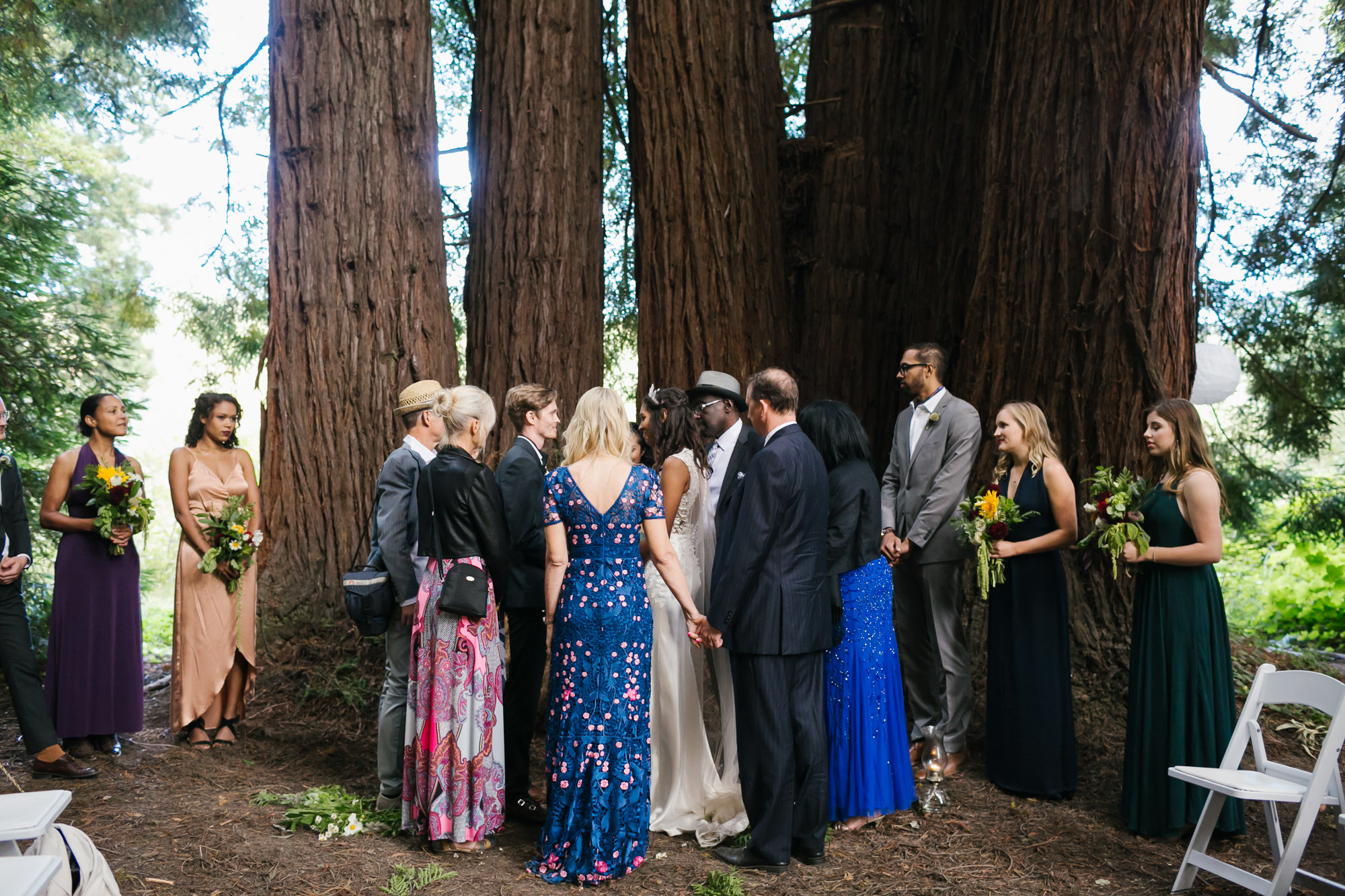 Family surround wedding couple during ceremony in a redwood grove