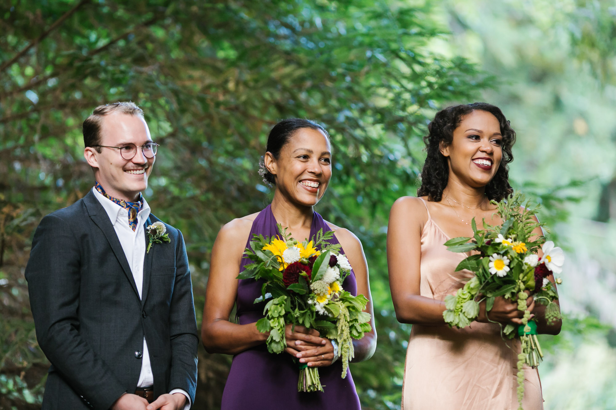Bridesmaids smile during wedding ceremony holding handmade bouquets