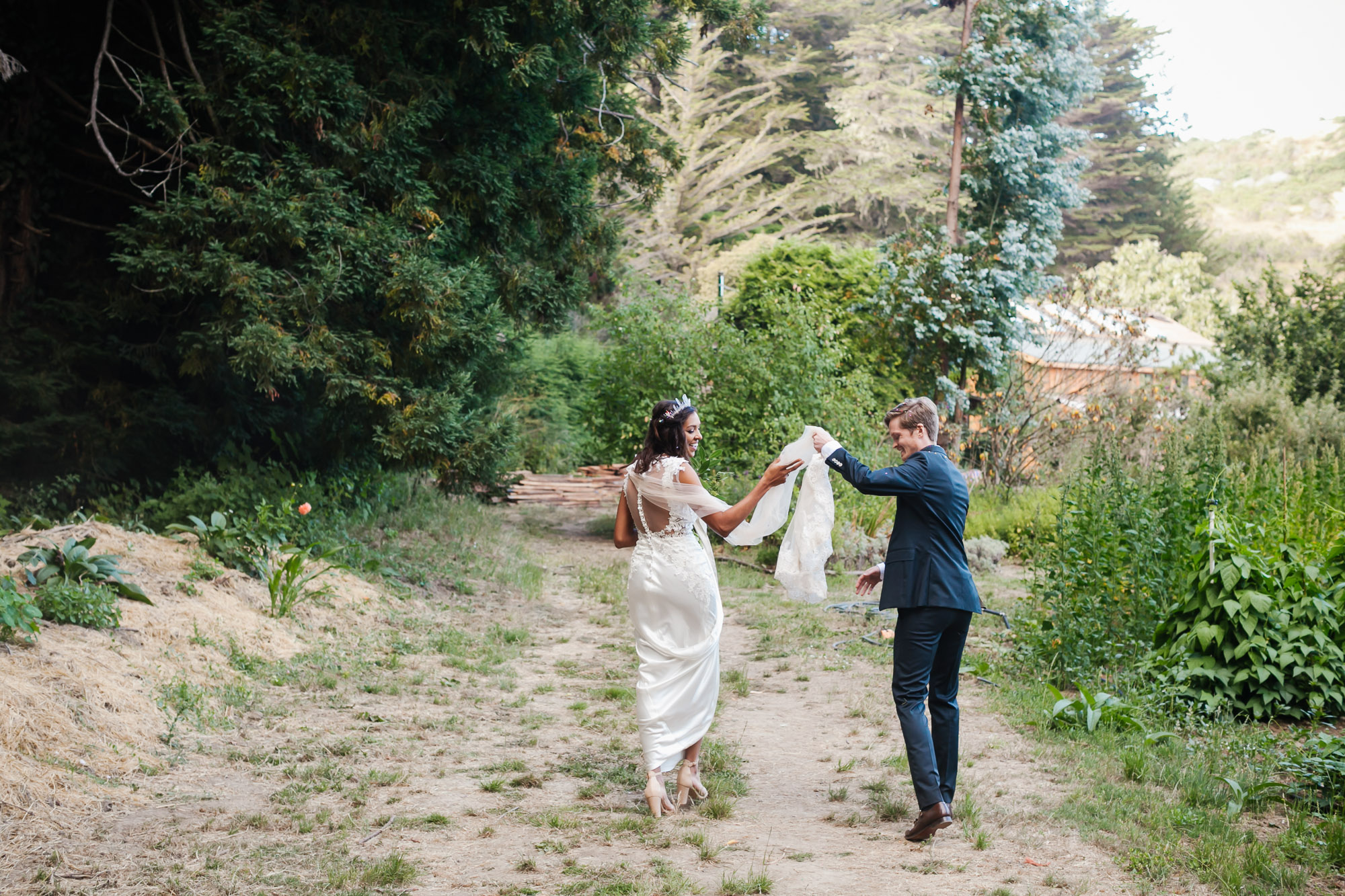 Groom helps his bride with her veil as they walk through coastal farm