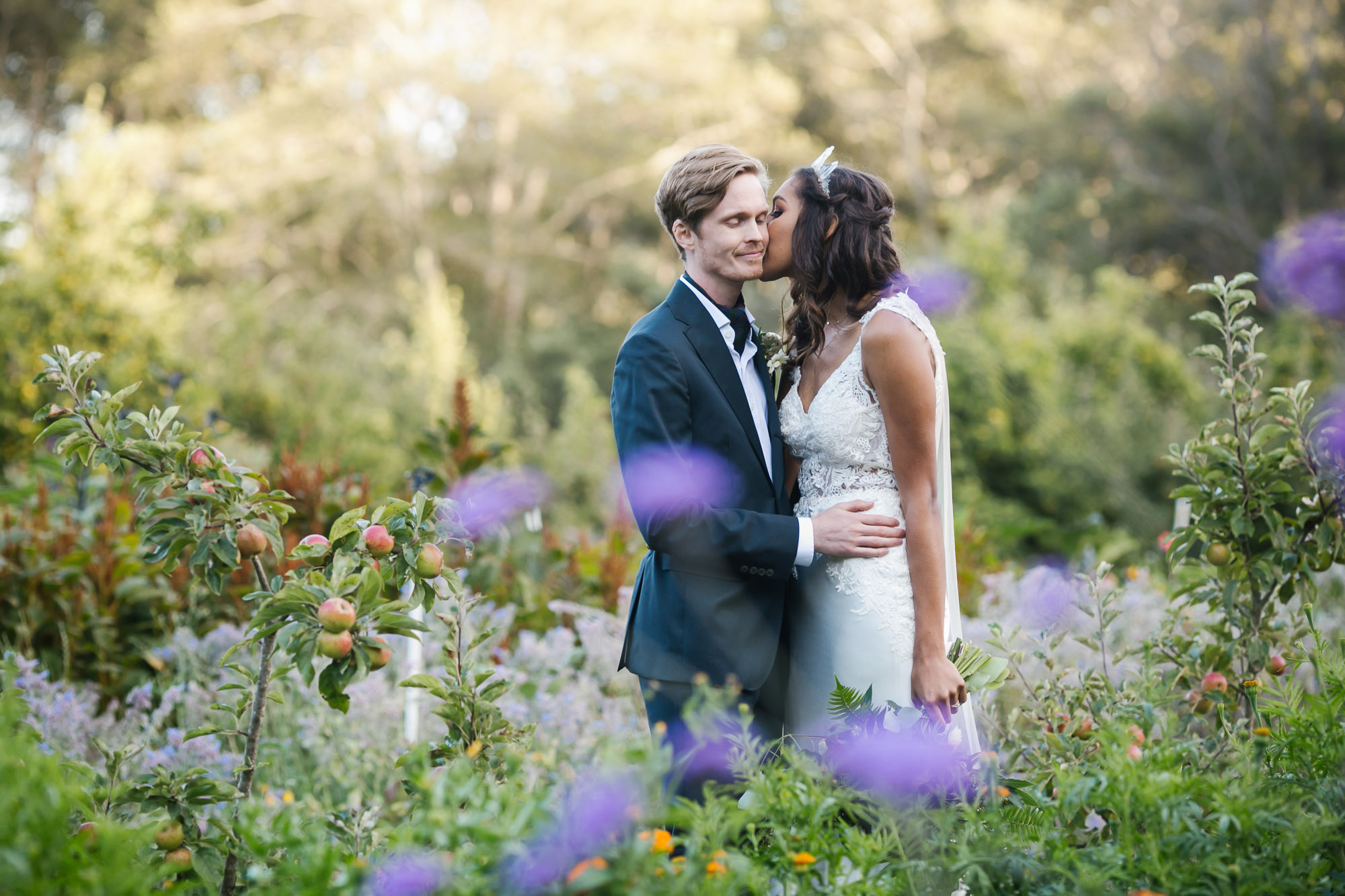 Bride in crystal crowns kisses her husband surrounded by flowers and apples