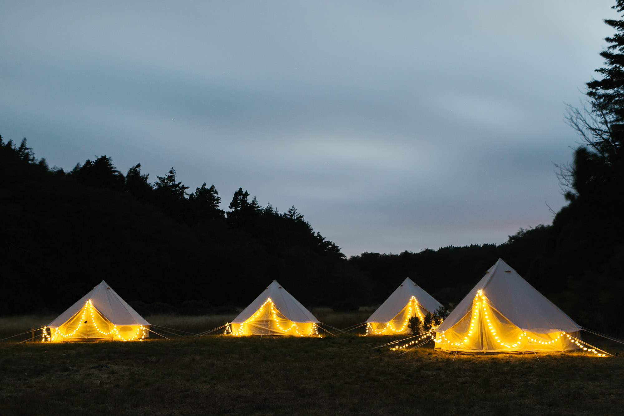 Glamping tents with twinkle lights in field at Oz Farm