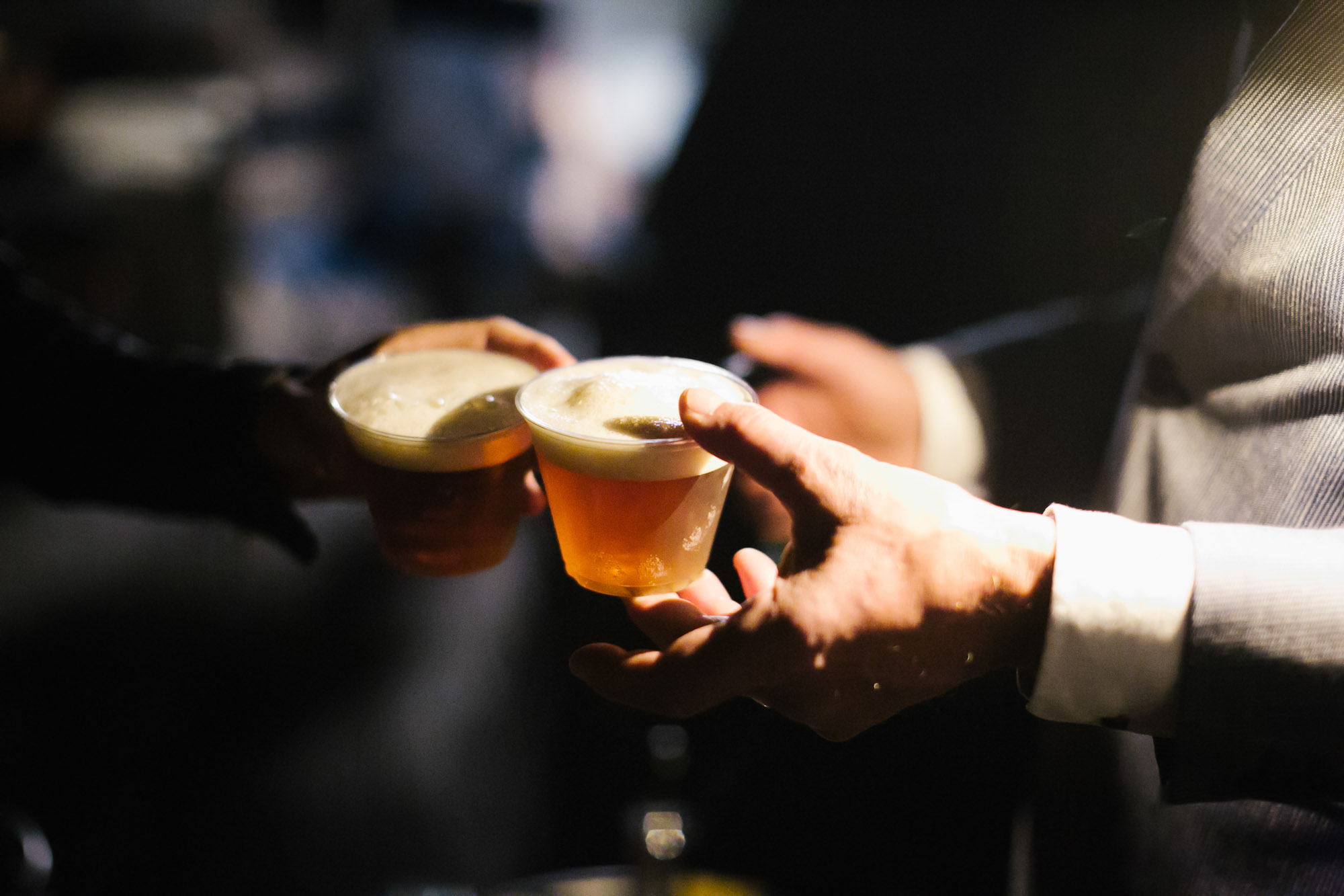 Wedding guests toast with beer at after party
