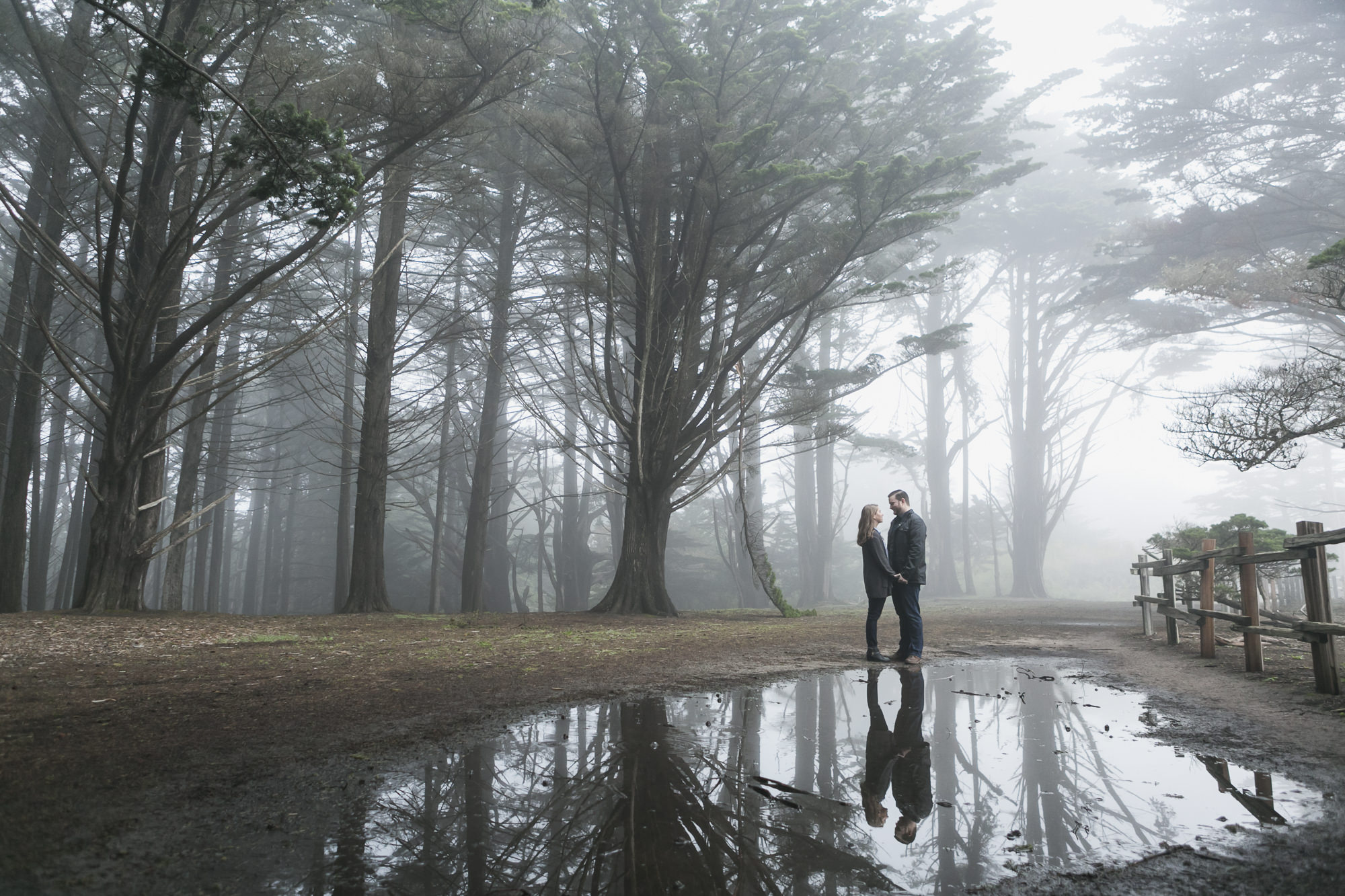 Couple are reflected in puddle in misty forest