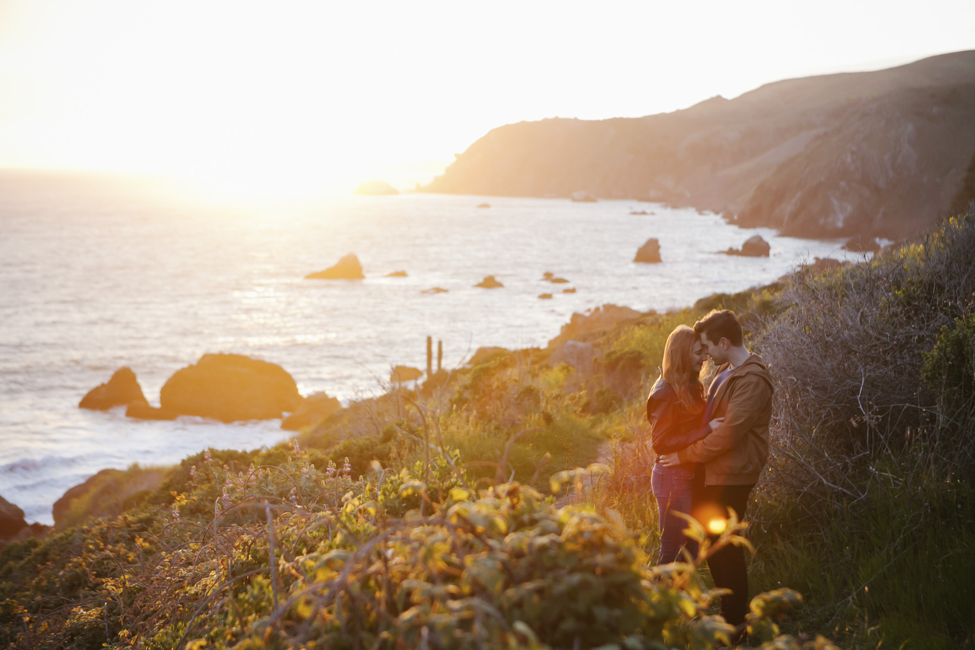 Couple snuggle at Slide Ranch on coast of California at sunset