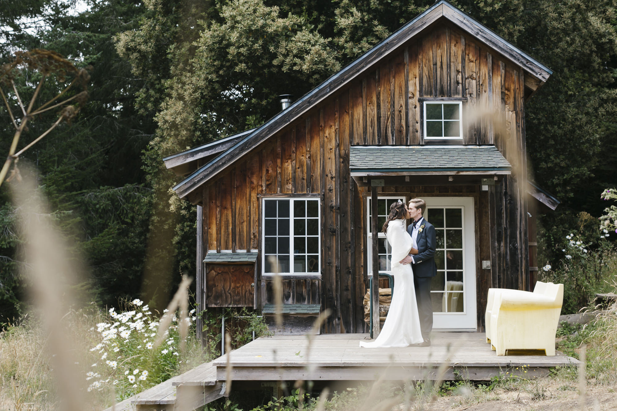 Wedding couple kisses in front of cabin on Mendocino farm