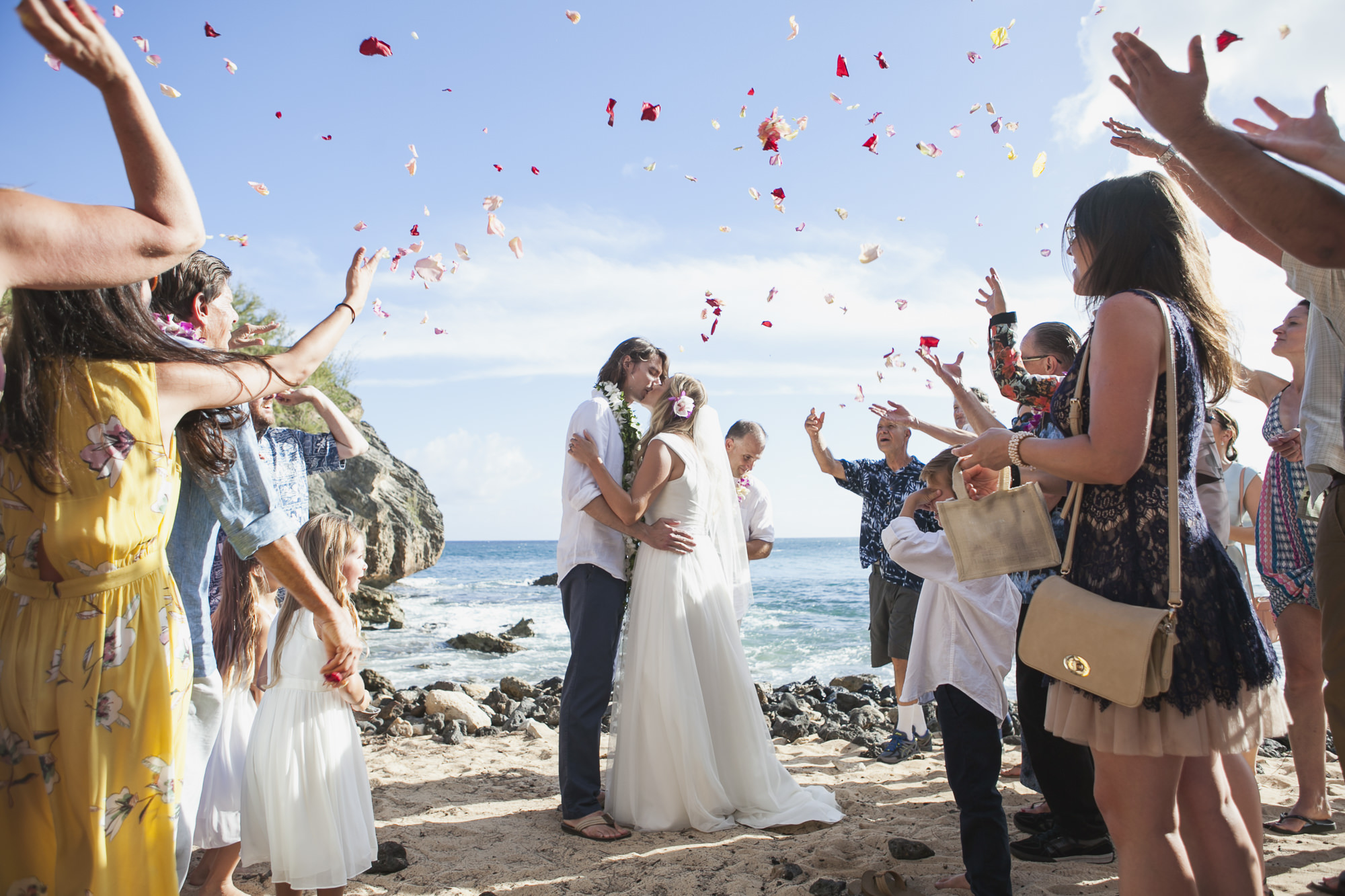 Wedding couple kiss on beach in Kauai with rose petals flying in celebration