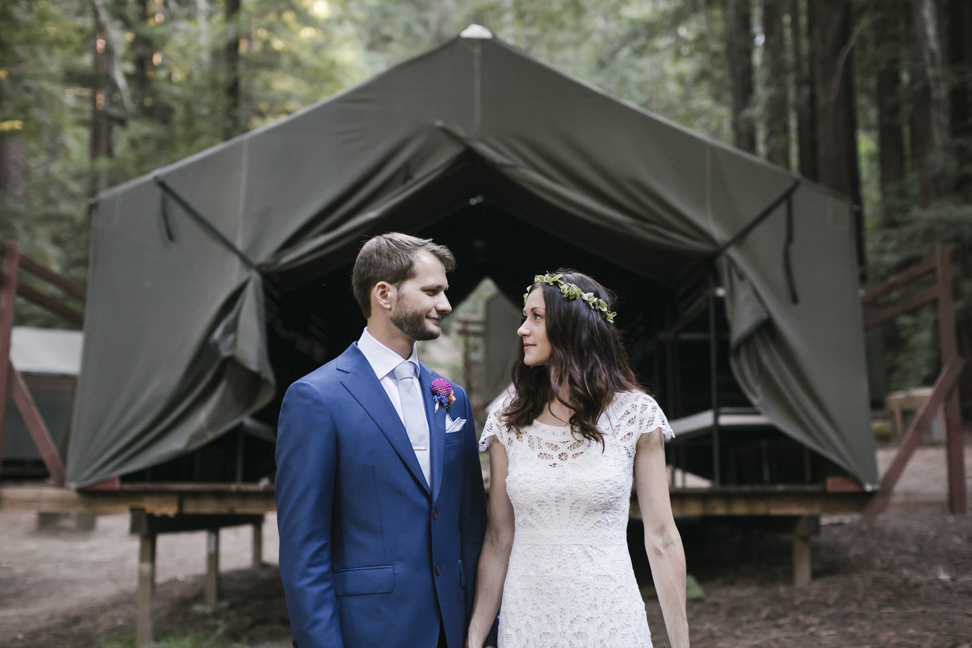 Wedding couple stand in front of tent cabin at Camp Campbell