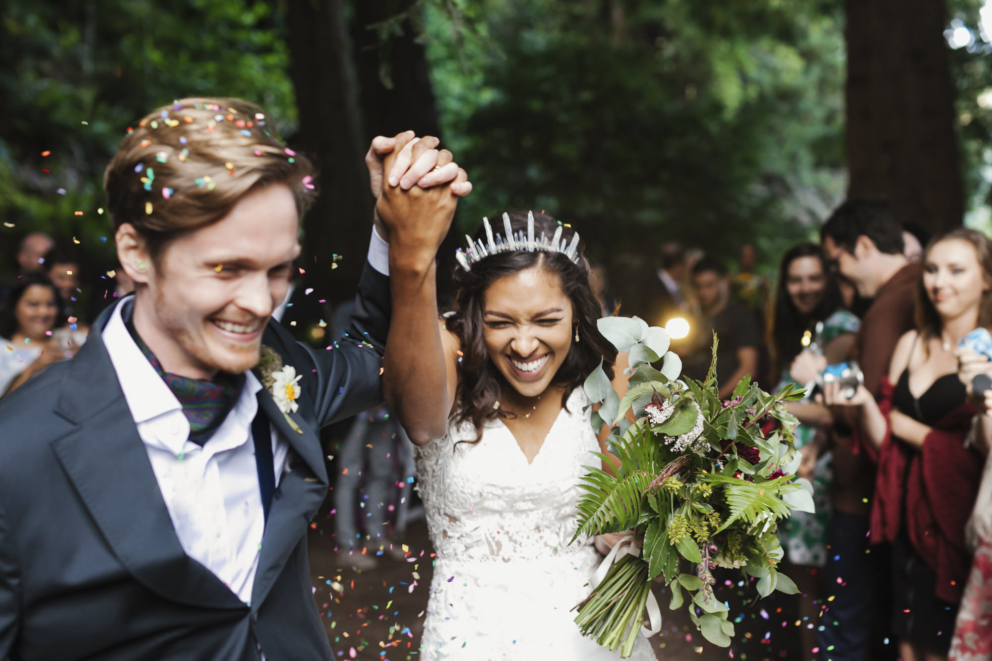 Wedding couple exit their redwood ceremony amidst confetti
