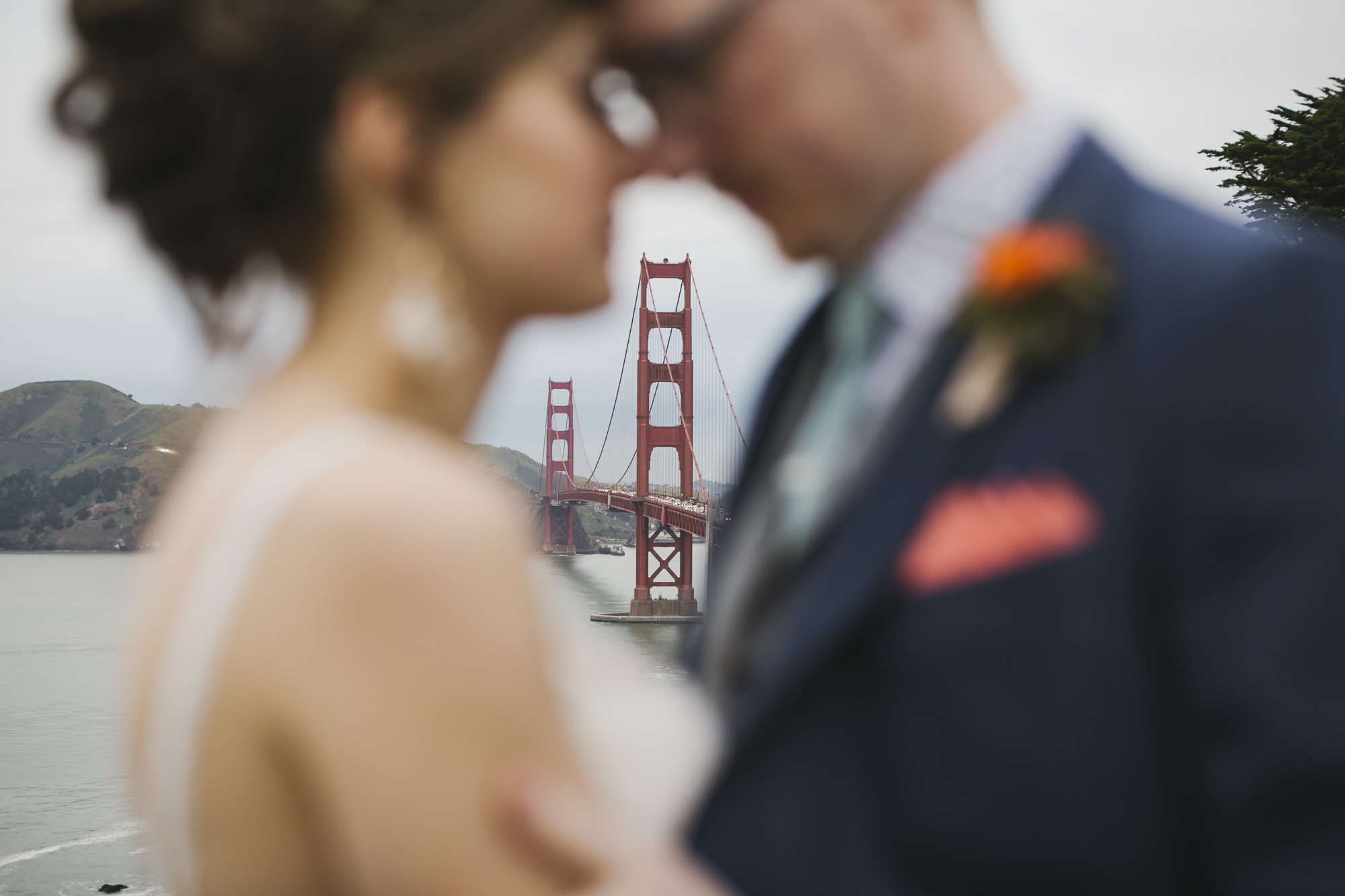 Wedding couple kiss in front of the Golden Gate Bridge on a foggy day