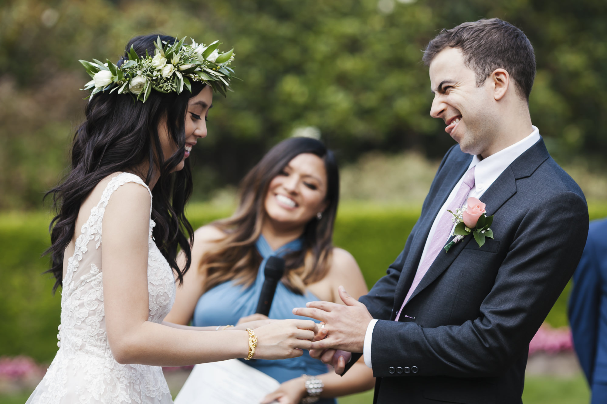 Bride has trouble getting wedding ring on her groom's finger while he makes a funny face
