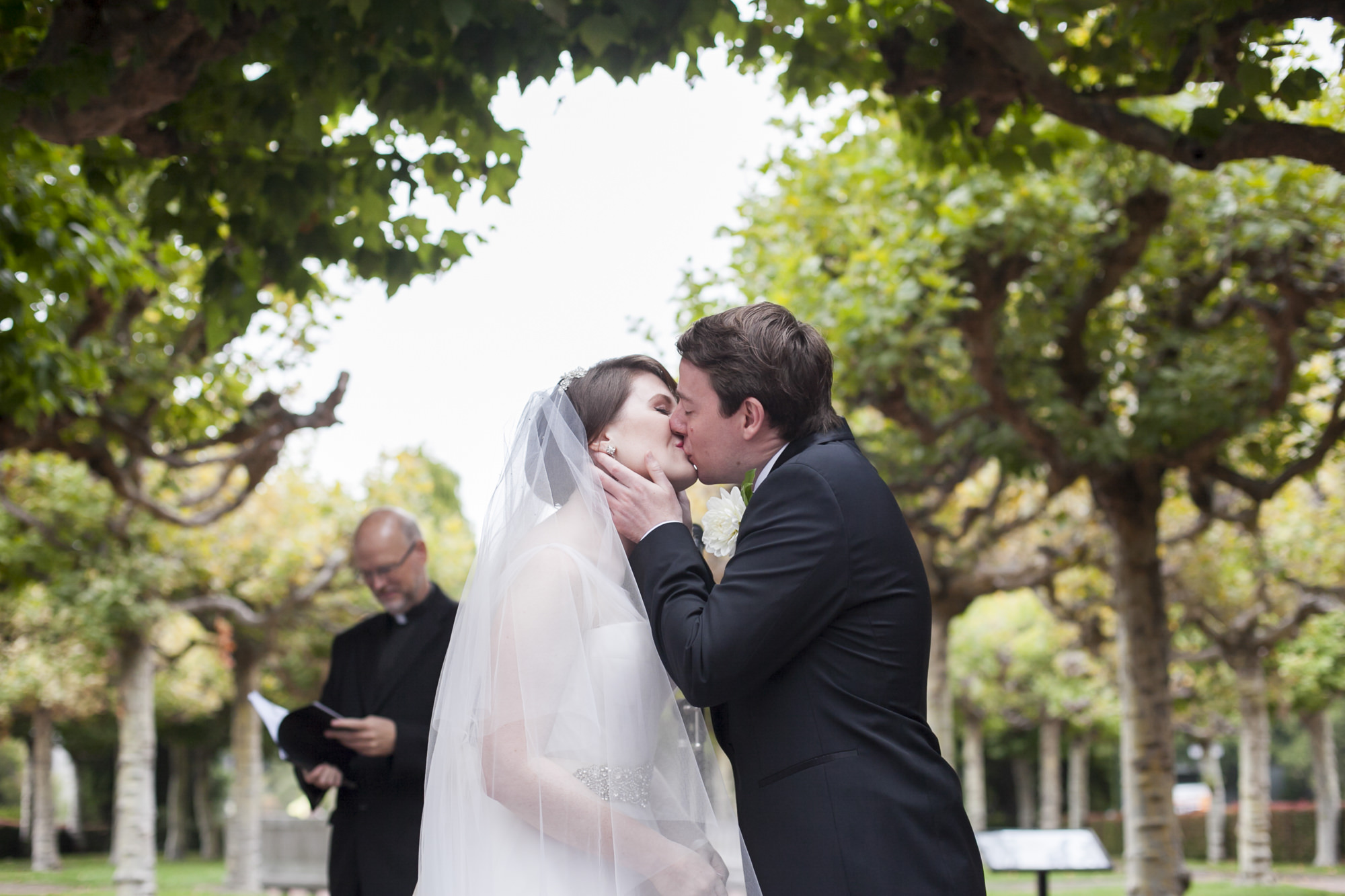 A couple's first kiss during their wedding ceremony at UC Berkeley